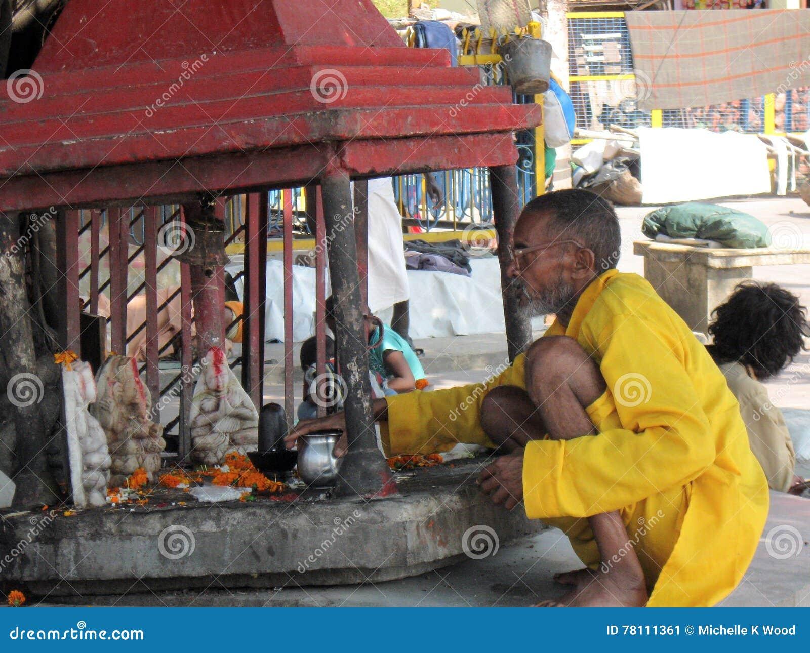 Indian Sadhu (holy man) tending a street shrine