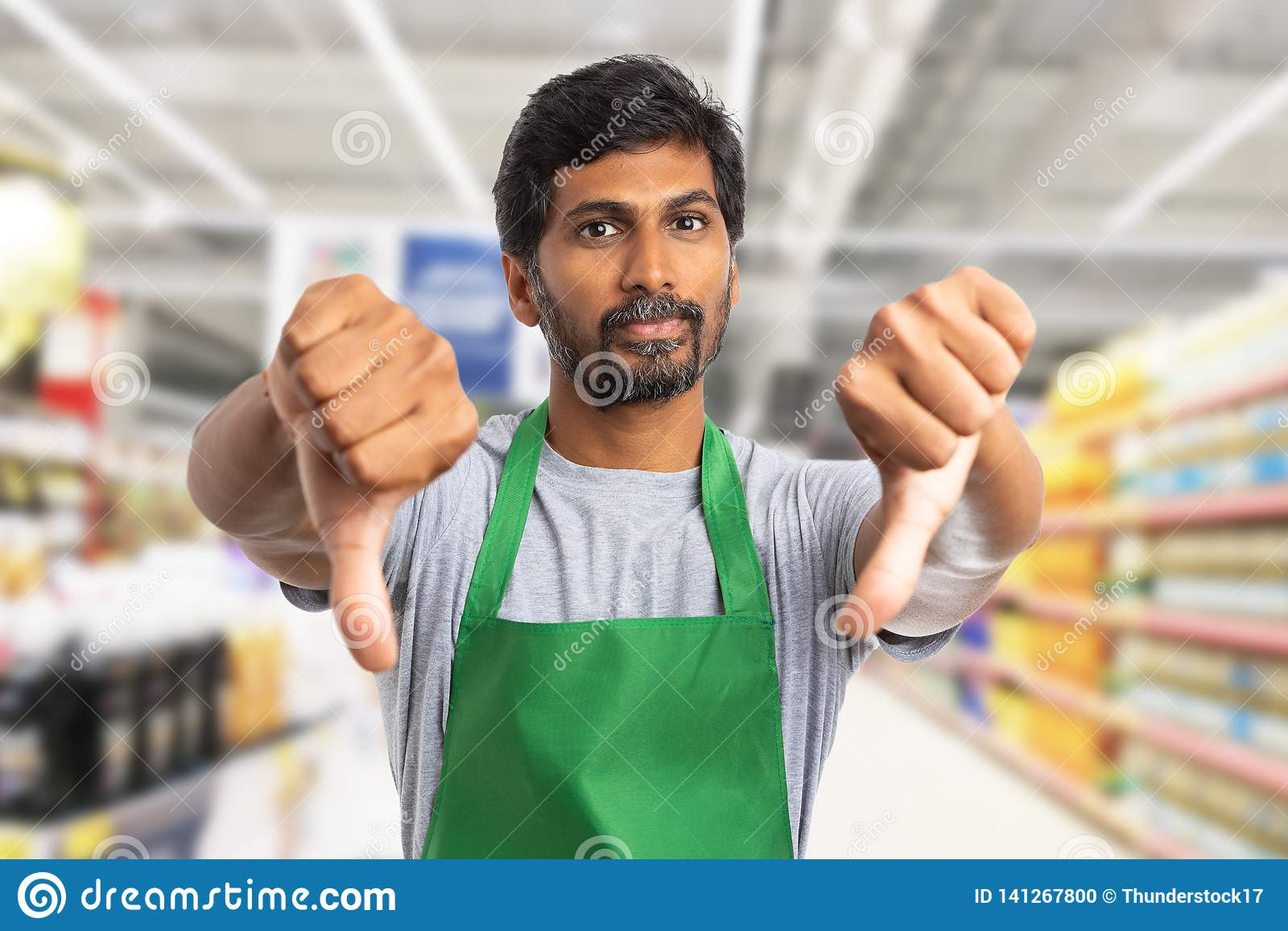 Supermarket worker making double thumbs-down gesture