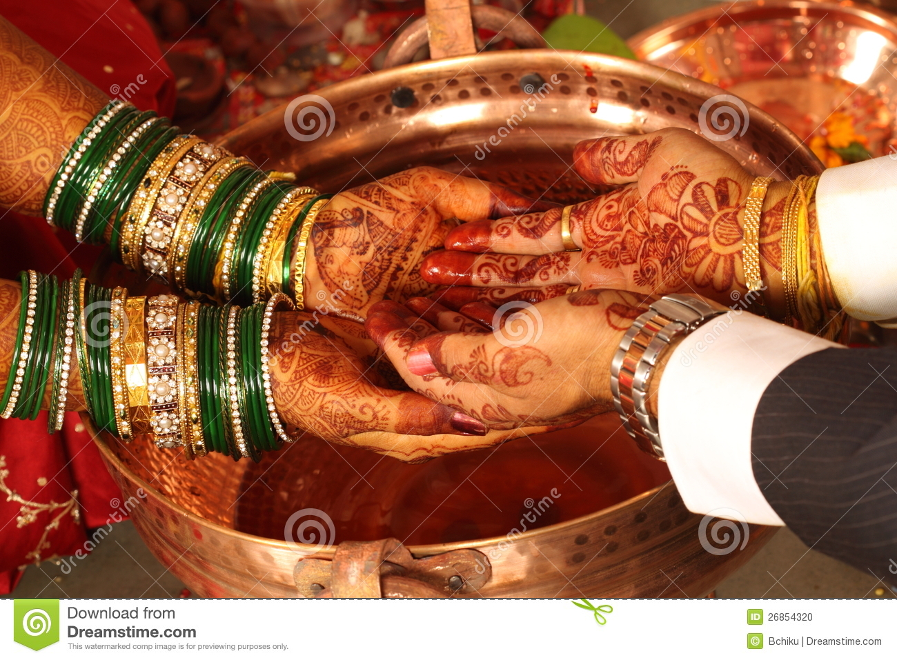 The hands of a bride and groom at an Indian wedding.