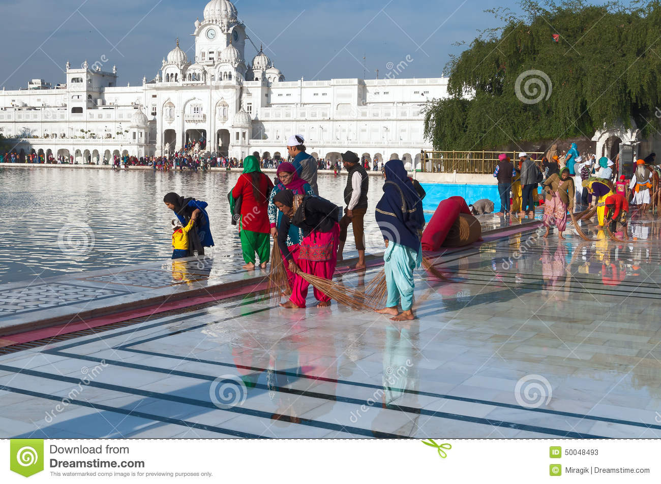Indian Women Clean Floor Near Golden Temple Before The