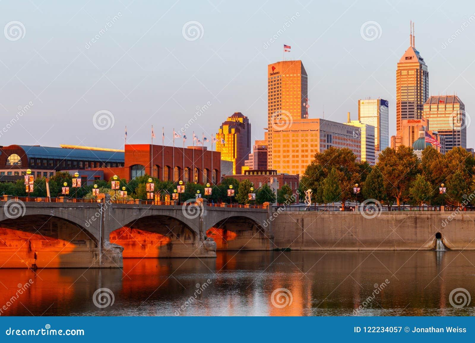 Indianapolis - circa im Juli 2018: Im Stadtzentrum gelegene Indianapolis-Skyline bei Sonnenuntergang mit Indy-Marksteinen der Sal