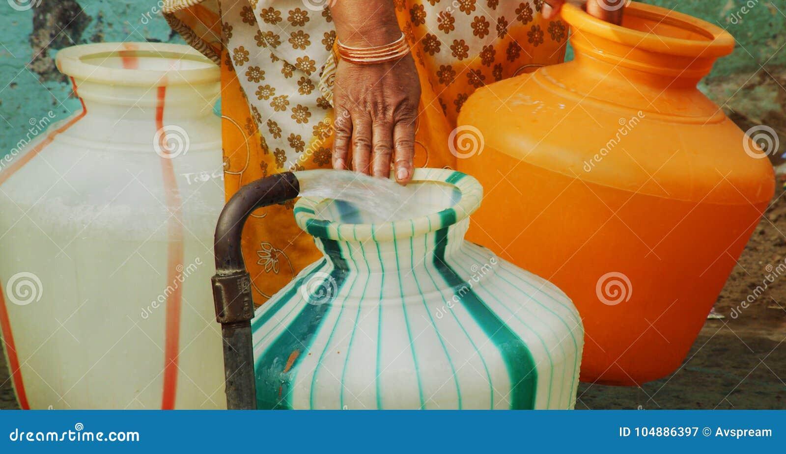 Indianin wody stojaka drymba wypełnia plastikowego wodnego garnek kobieta niesie wodnego garnek