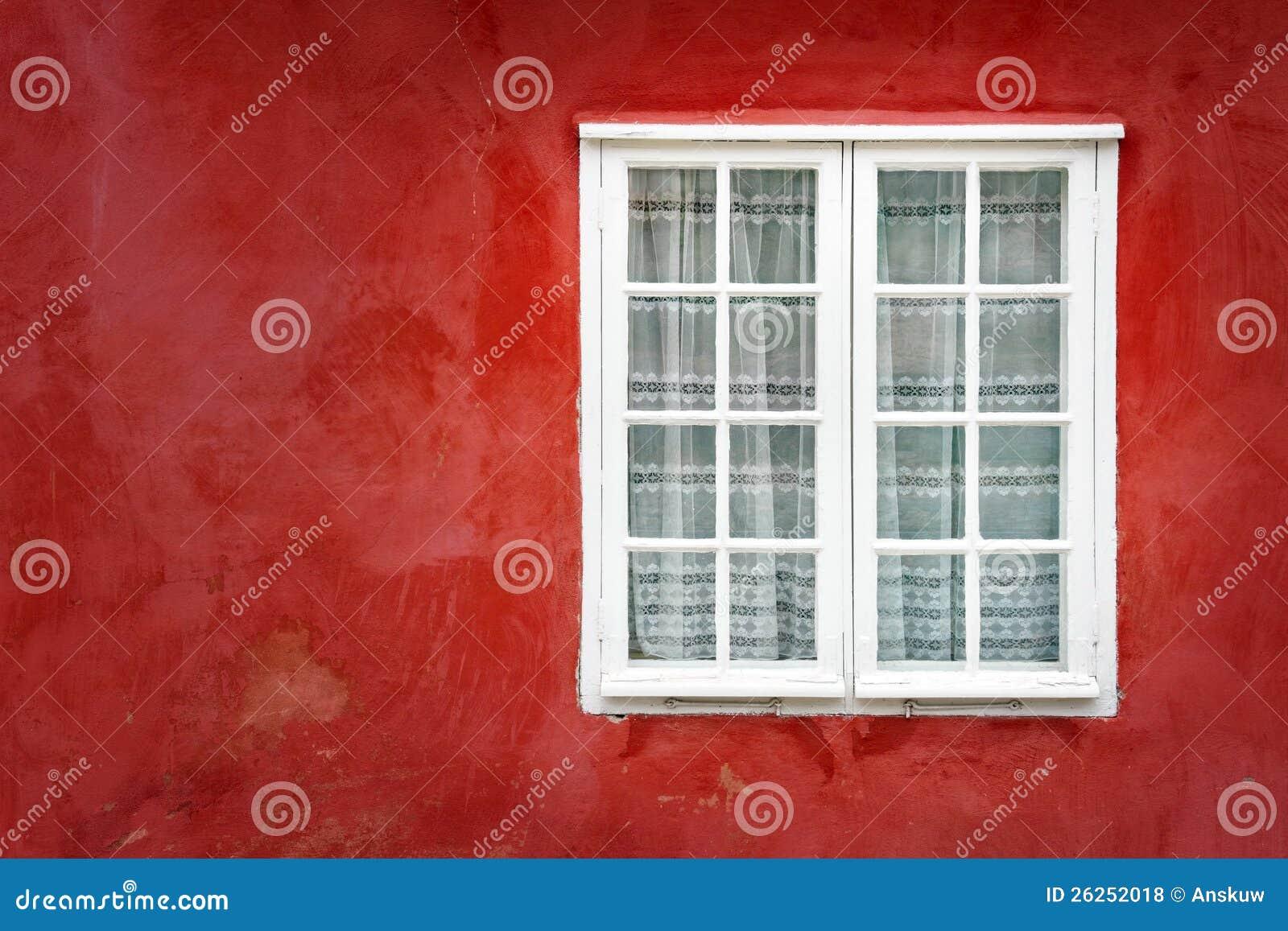 Indicador decorativo em uma parede vermelha velha do estuque