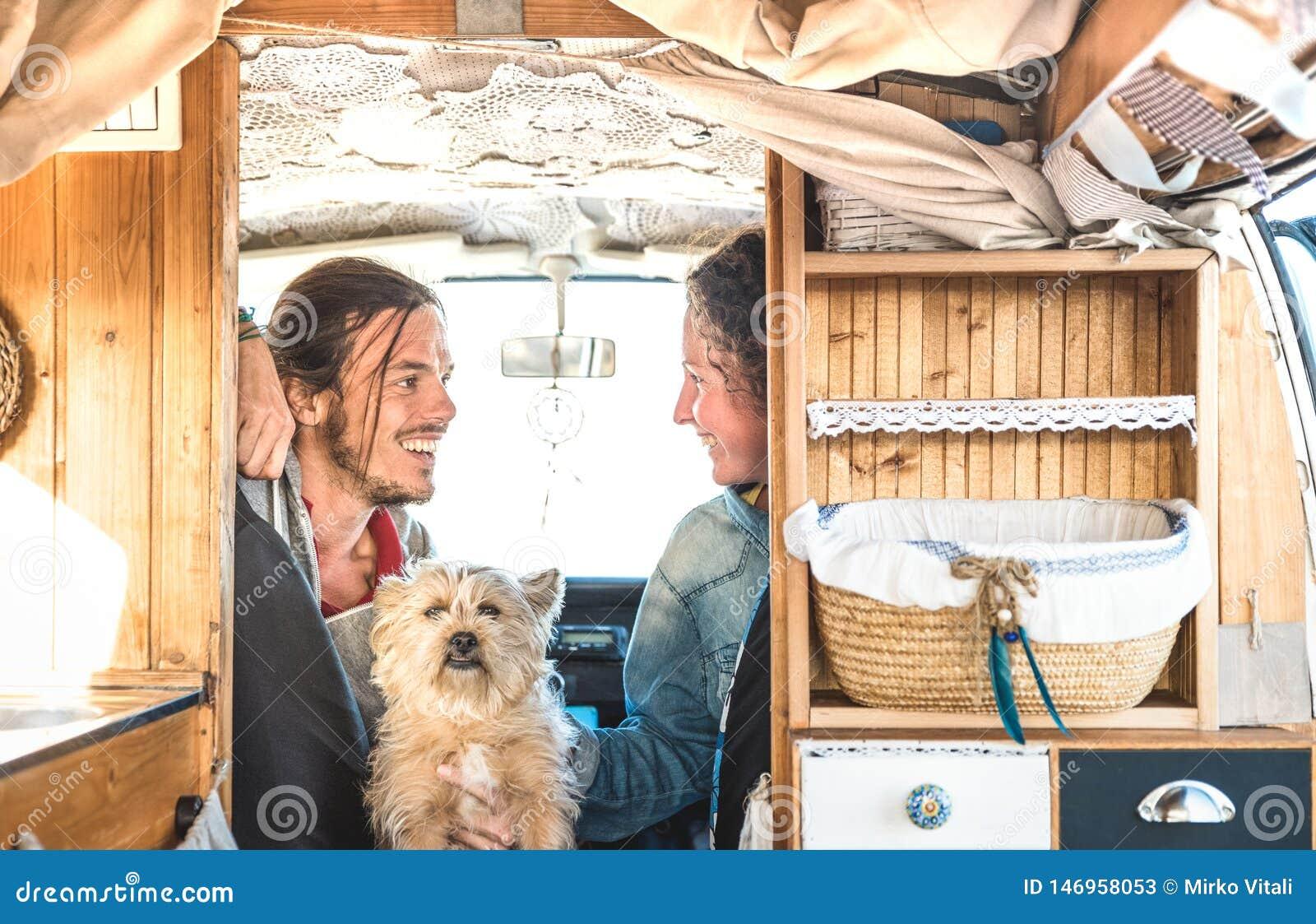 Indie Paare mit wenigem Hund, der zusammen auf Oldtimerminipackwagentransport - Reiselebensstilkonzept mit Hippie-Leuten reist