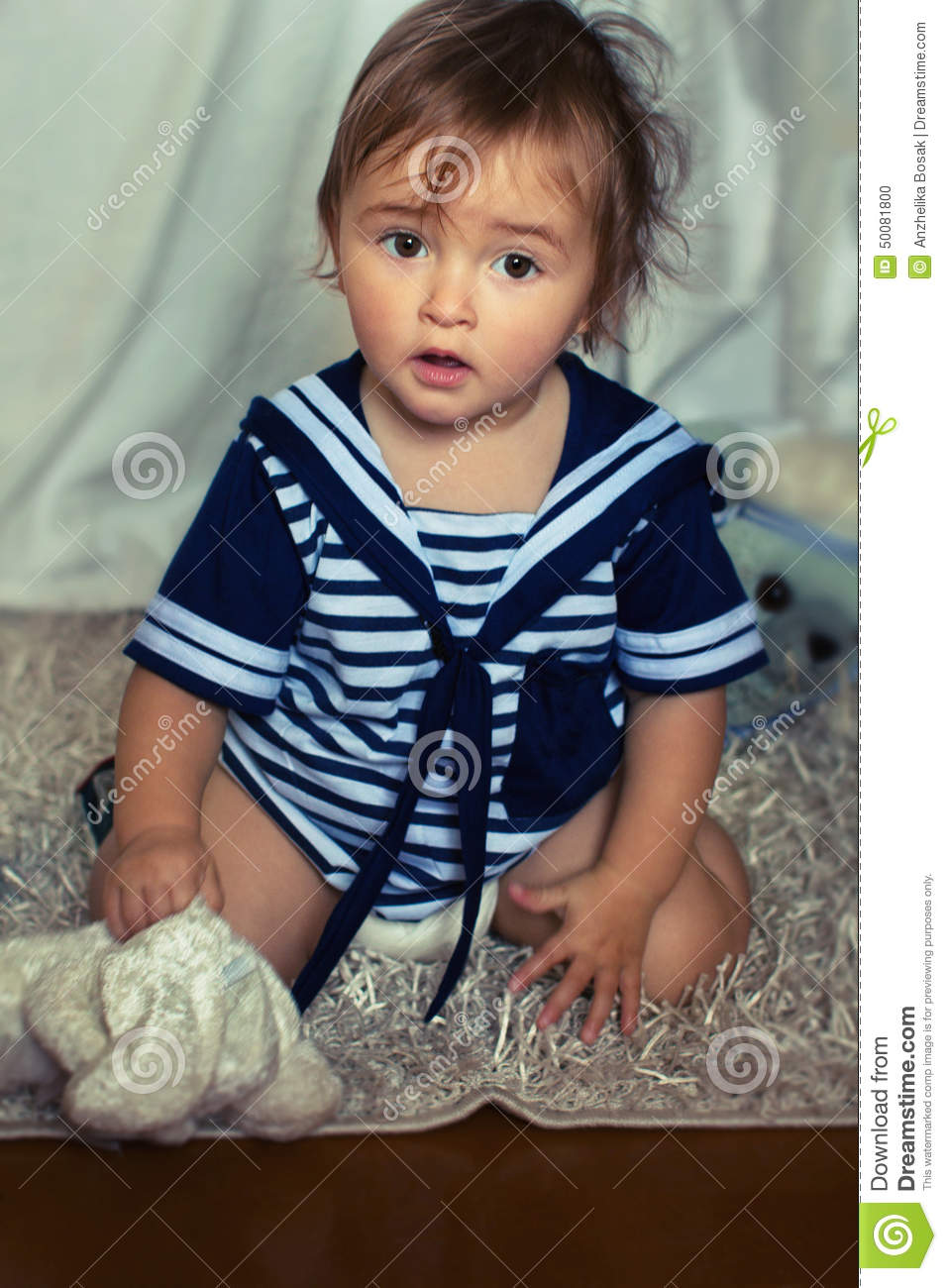Indignant baby girl in the nautical striped vest sits