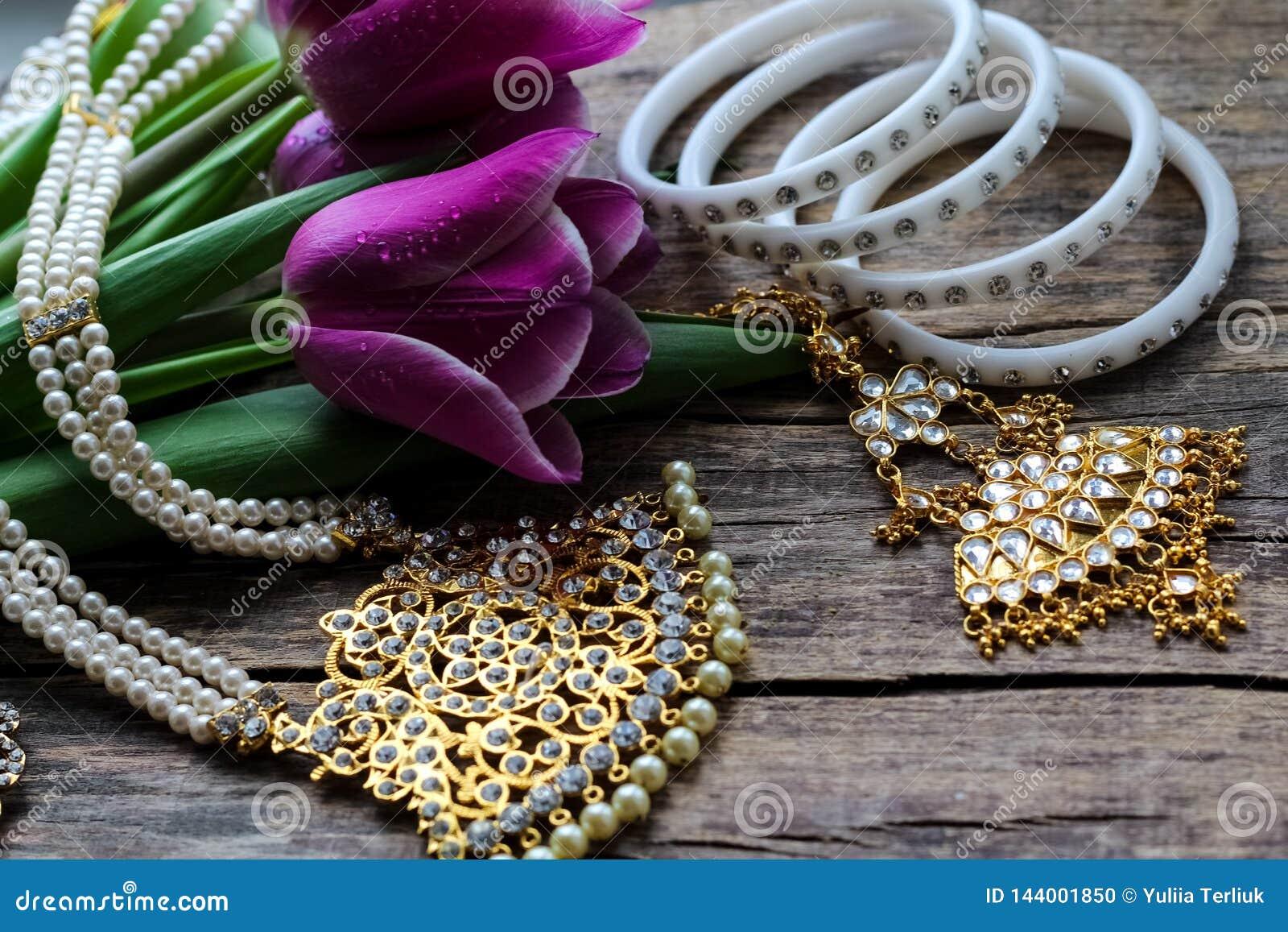 Indische decoratie voor het dansen: armbanden, halsband Purpere ultraviolette tulpen op oude rustieke houten achtergrond