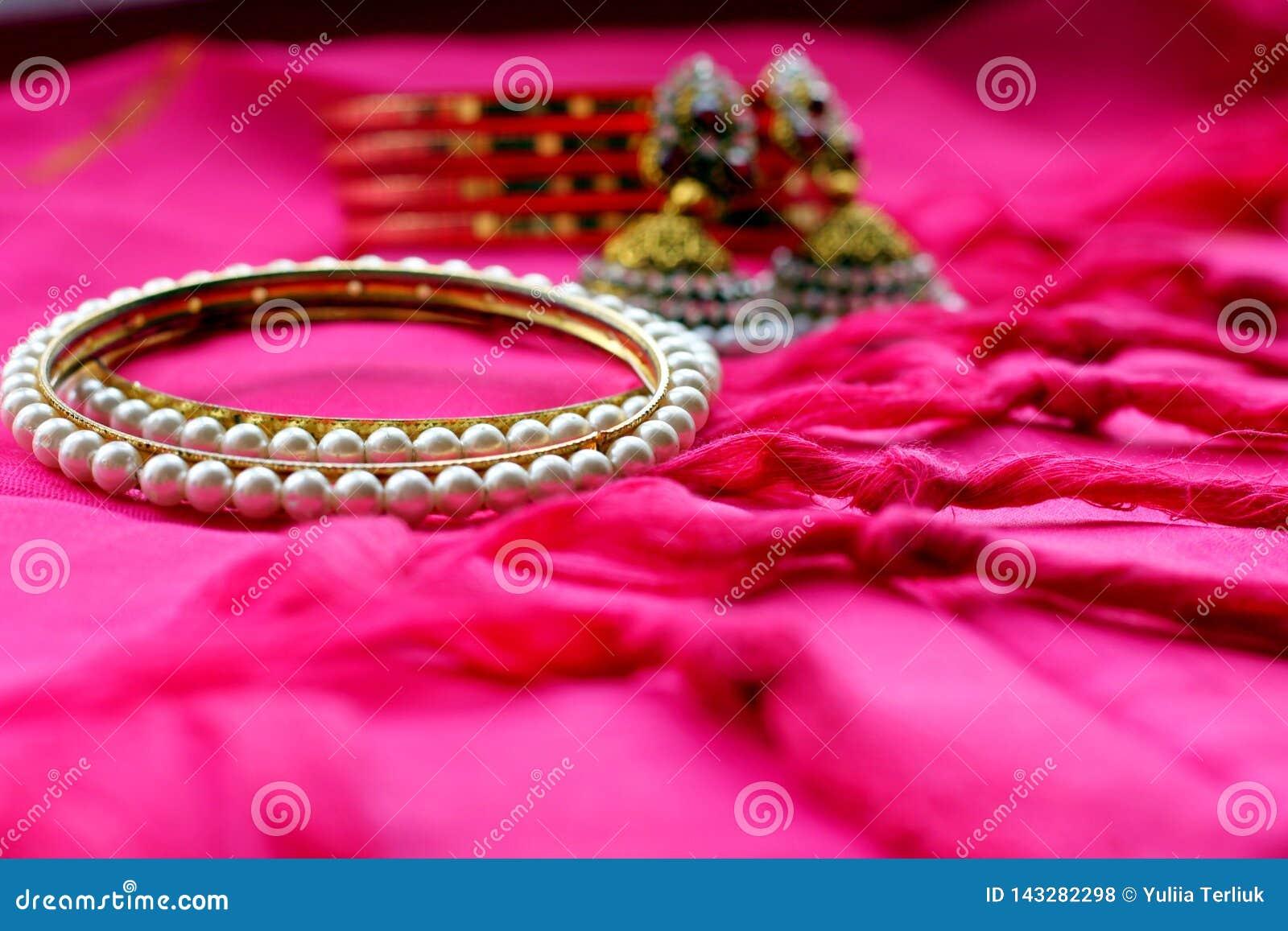 Indische etnische juwelenarmbanden en oorringen op roze stof