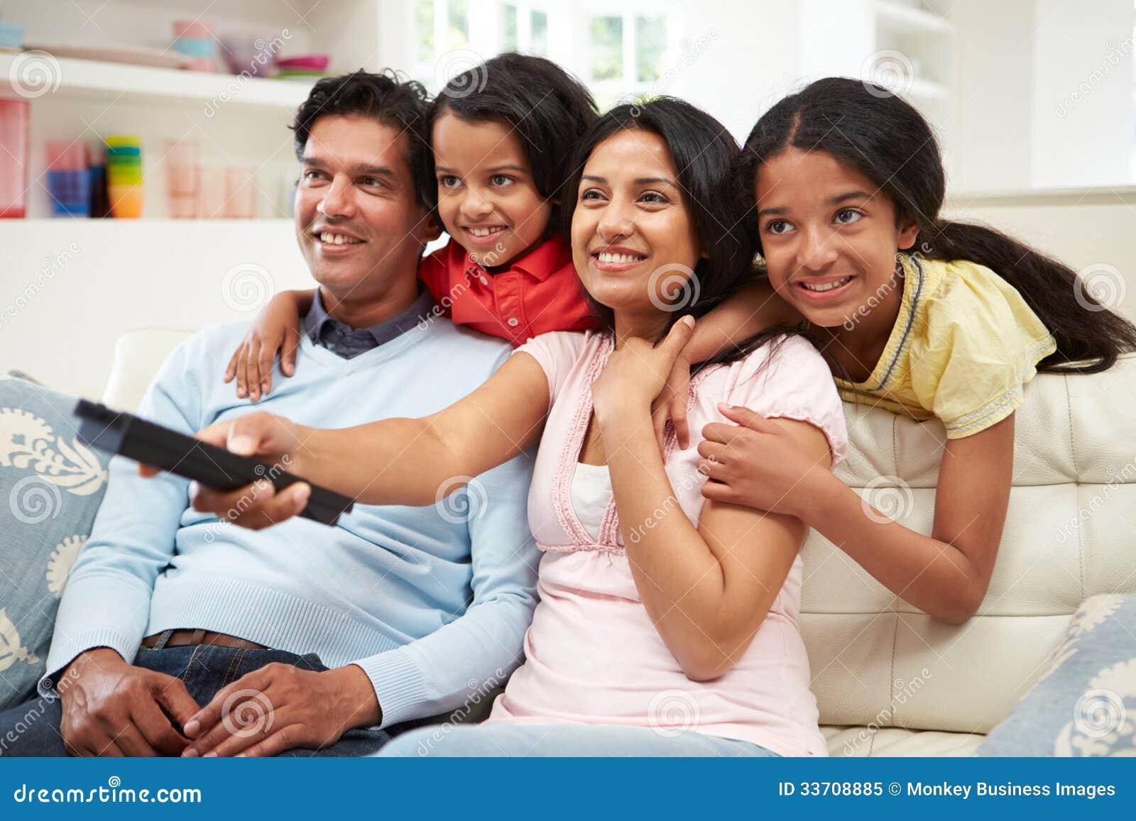 Indische familiezitting op sofa watching tv samen royalty for Indisches sofa