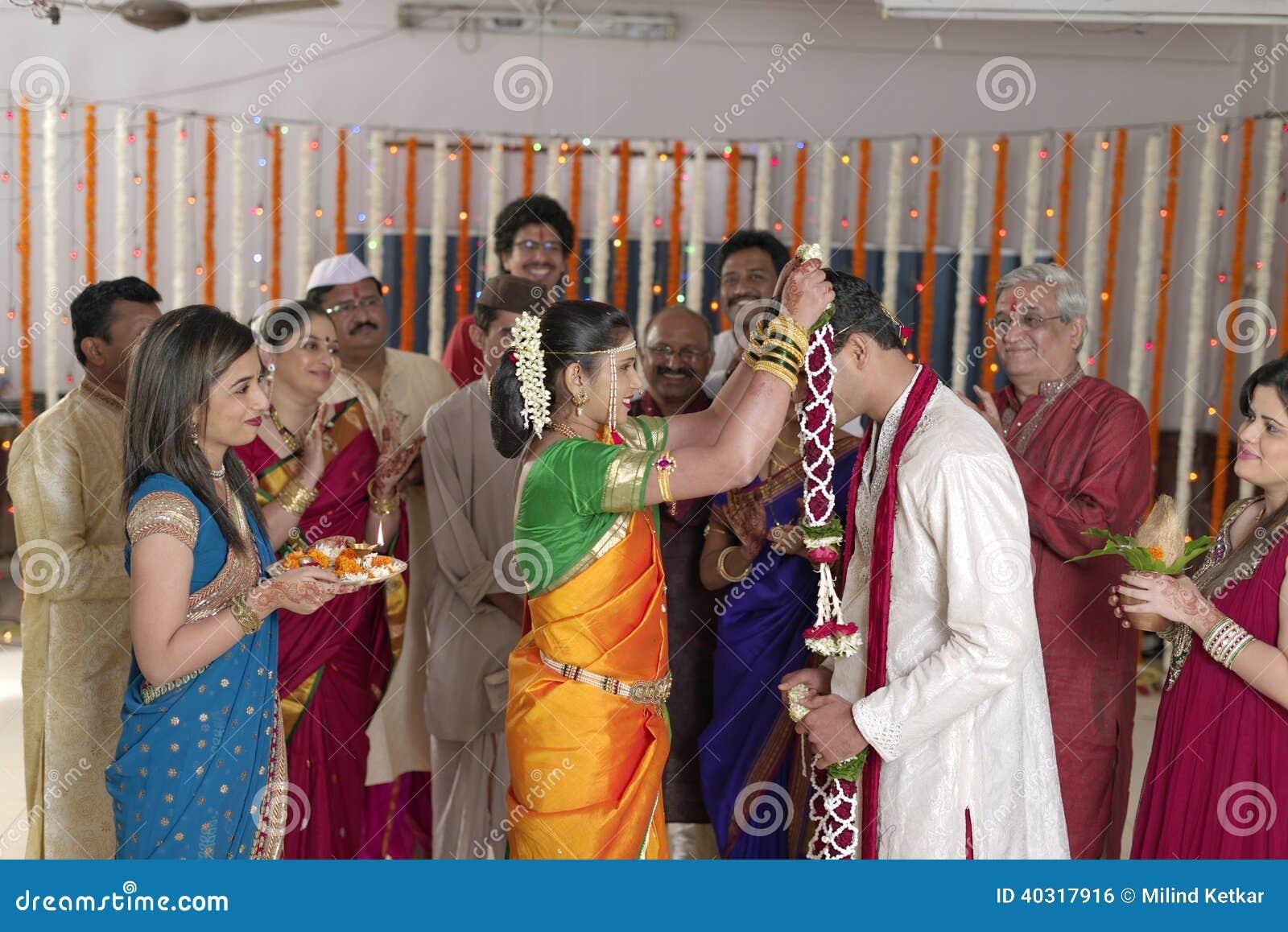 Indische hindische Braut, die Bräutigam betrachtet und Girlande in der Maharashtrahochzeit austauscht