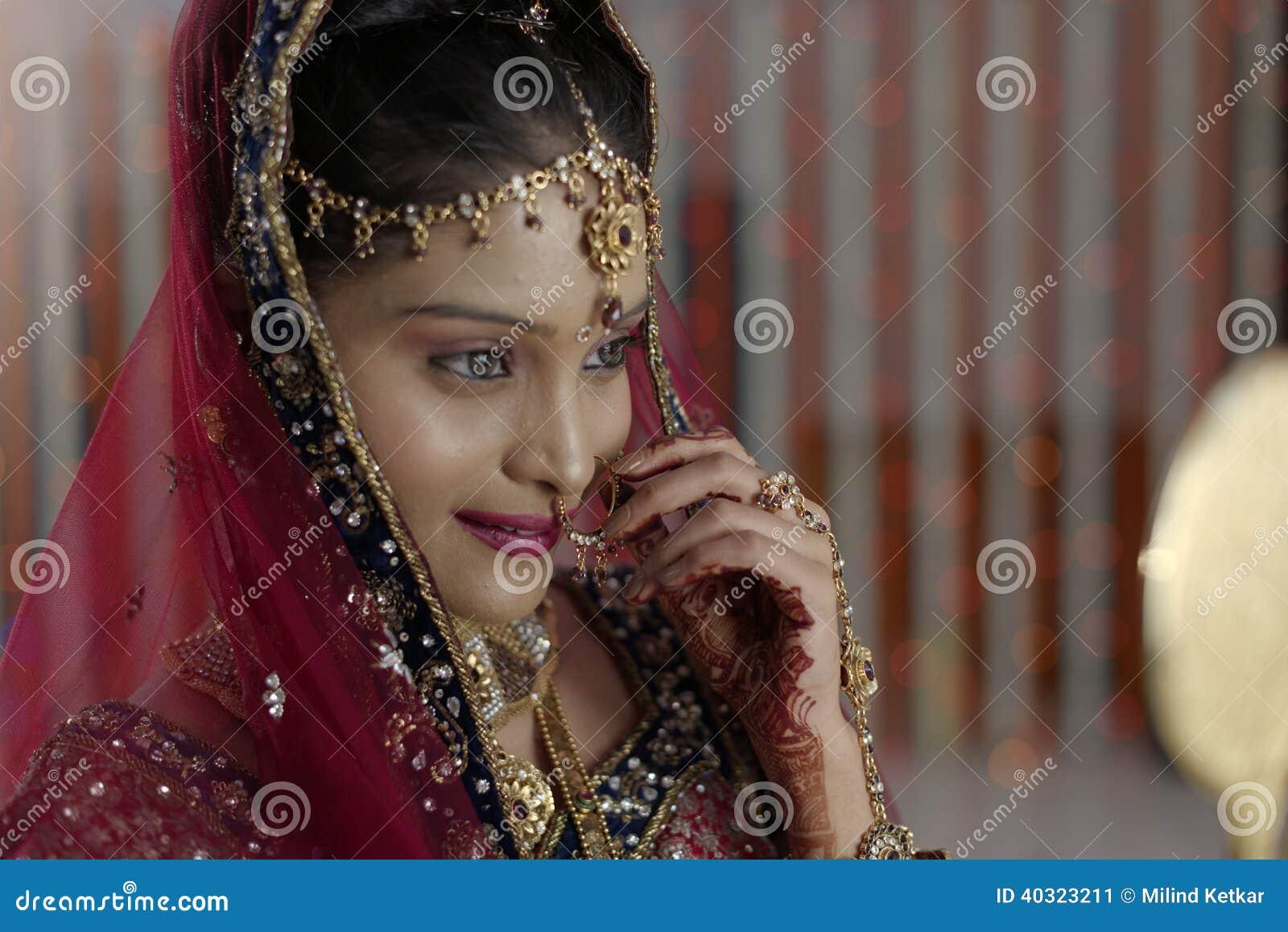 Indische Hindoese Bruid die met juwelen in spiegel kijken.
