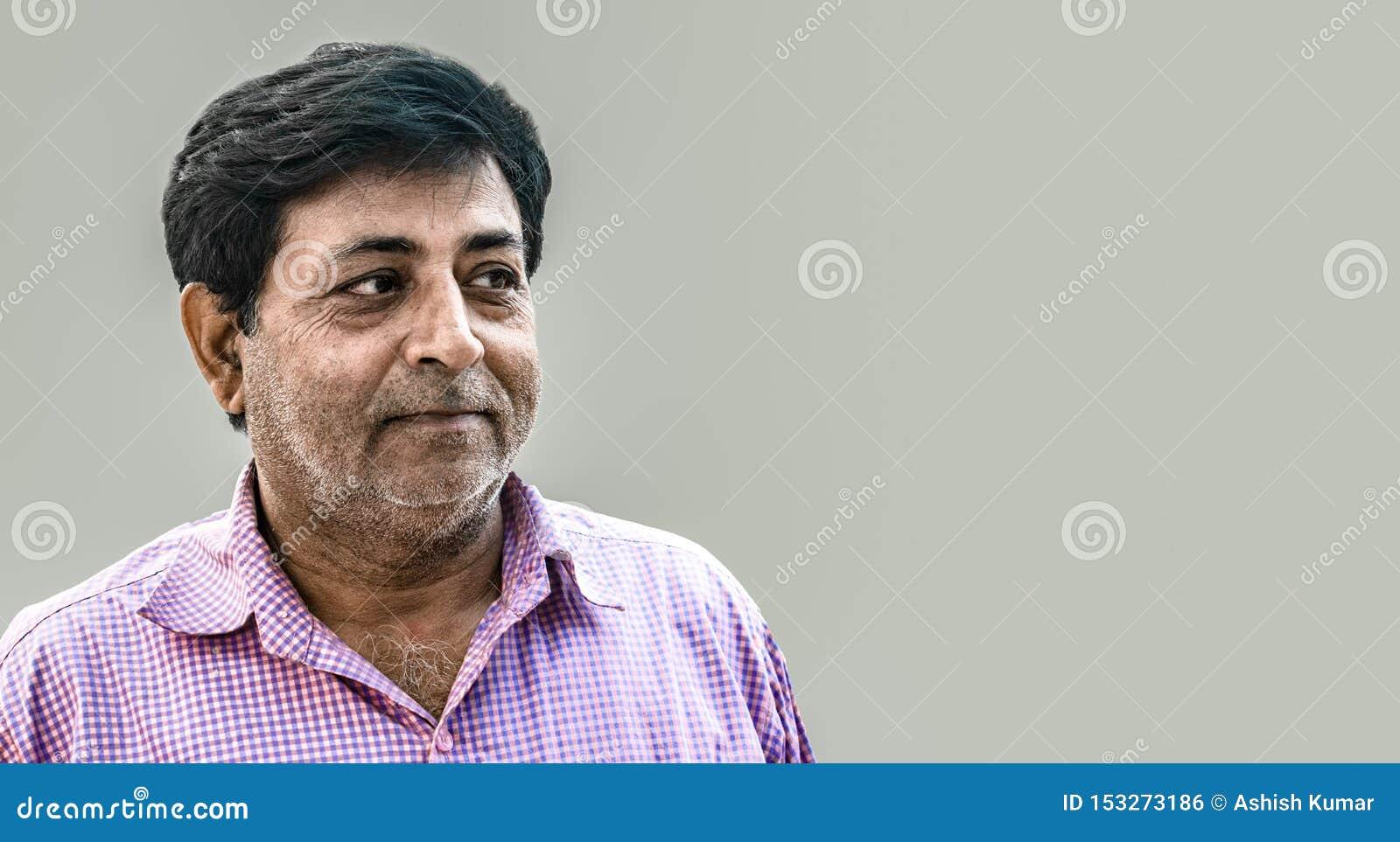 Indische mens die op middelbare leeftijd uitdrukking die van tevredenheid geven, purper controleoverhemd dragen Het kenmerken van