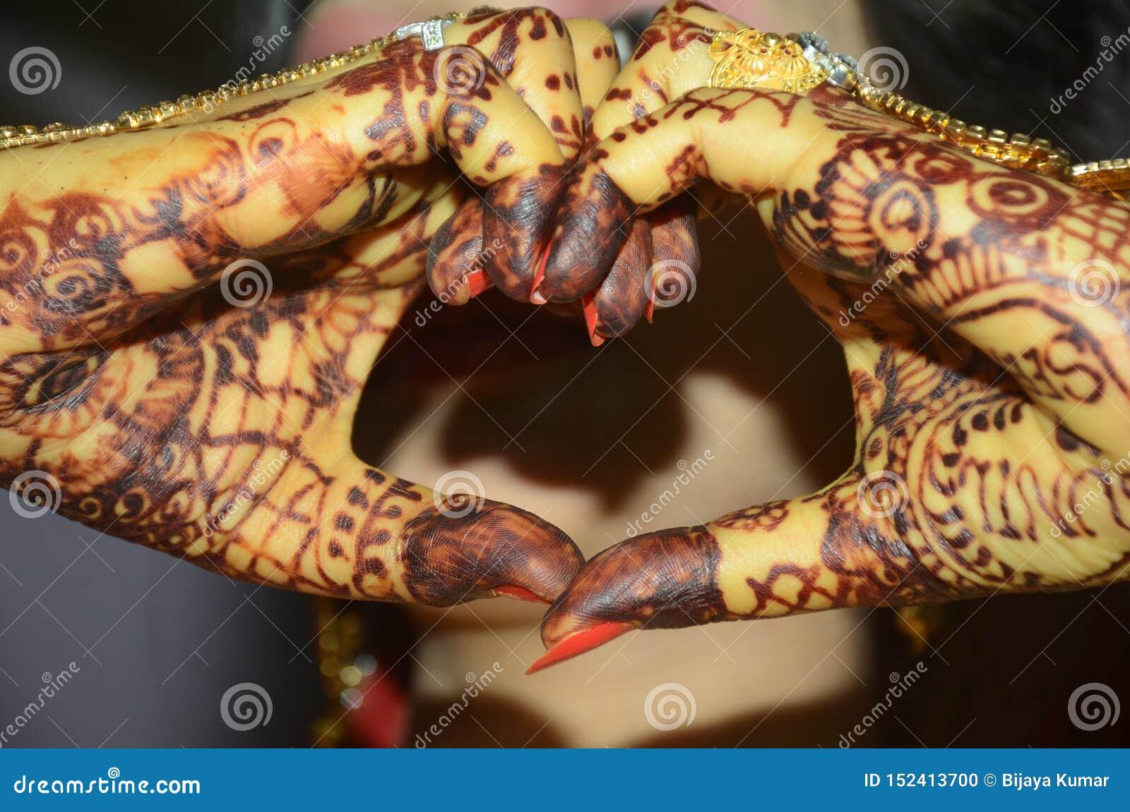 Indischer Bräutigam, der ihre Hand als schöner Nahaufnahmeschuß der Herzform formt
