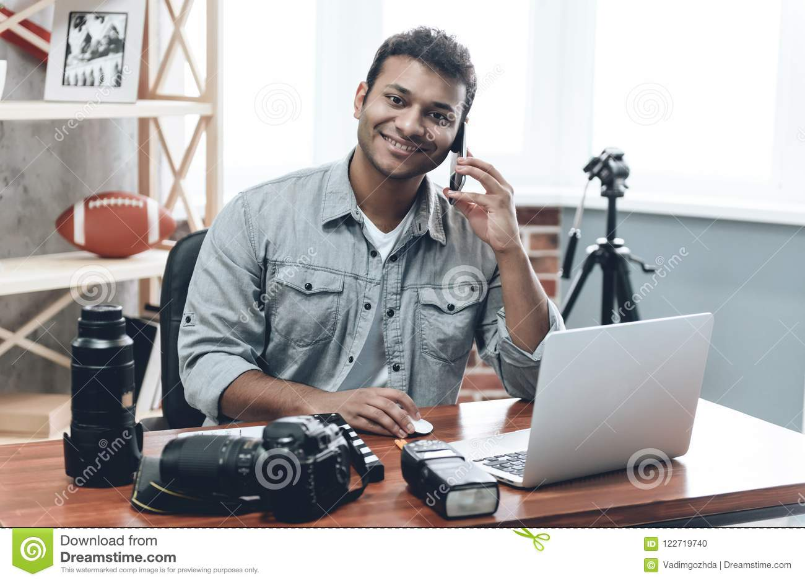 Indischer glücklicher junger Mann-Fotograf Work vom Haus