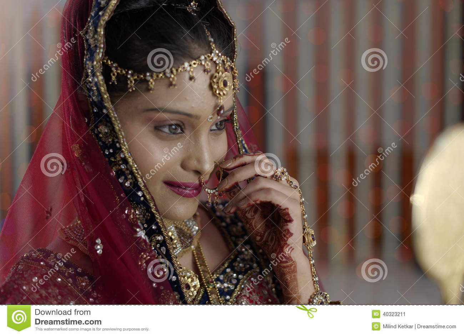 Indisk hinduisk brud med smycken som ser i spegel.
