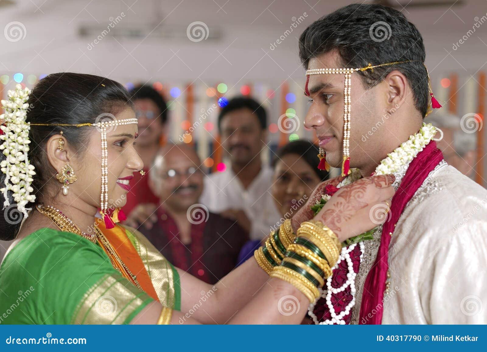 Indisk hinduisk brud som ser brudgummen och utbyter girlanden i maharashtrabröllop