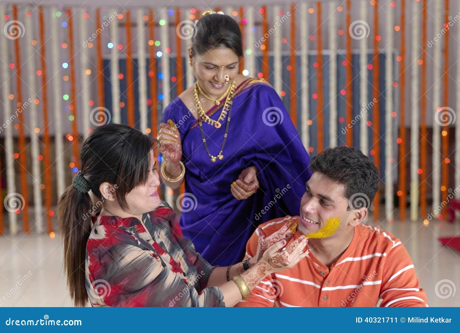 Indisk hinduisk brudgum med gurkmejadeg på framsida med modern