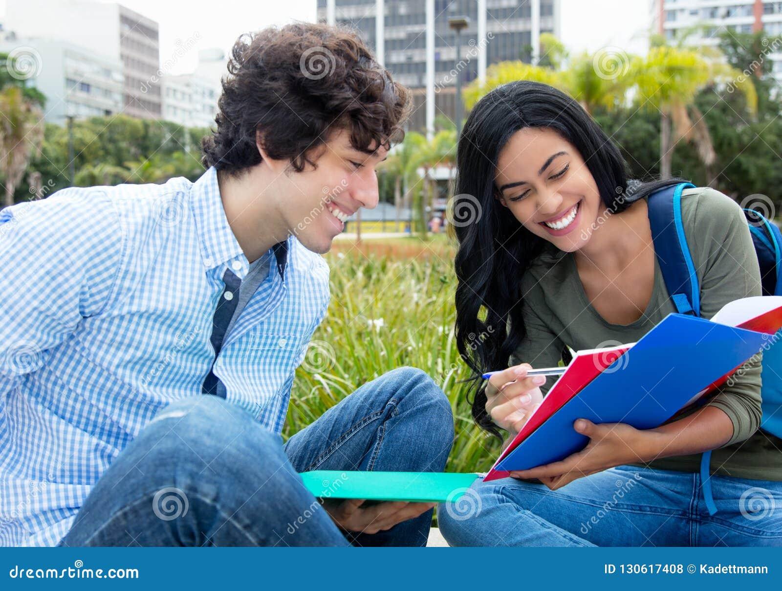 Indisk kvinnlig student som lär med den caucasian manliga studenten