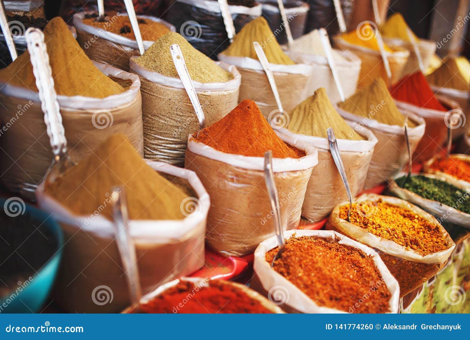 Indiska kulöra kryddor på den lokala marknaden En variation av kryddor av olika färger och skuggor, anstrykningar och texturer på
