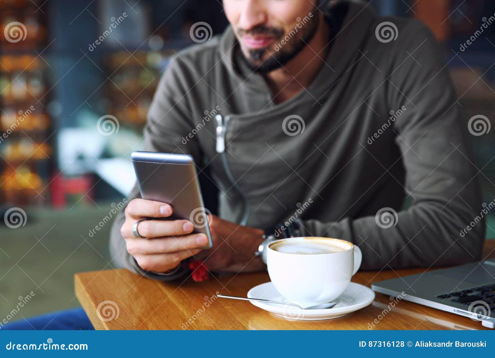 Indivíduo alegre considerável novo do moderno no restaurante usando um telefone celular, mãos perto acima Foco seletivo