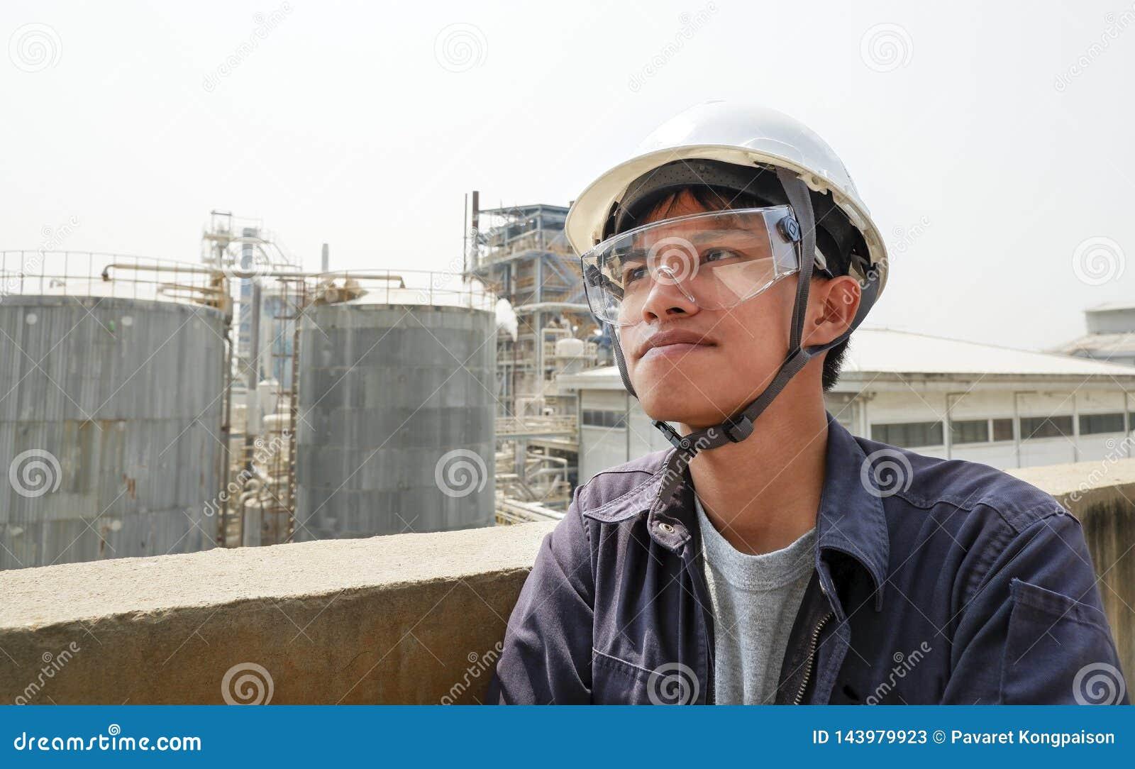 Indivíduo asiático que veste um funcionamento do capacete em uma grande fábrica industrial que verifica o processo de produção