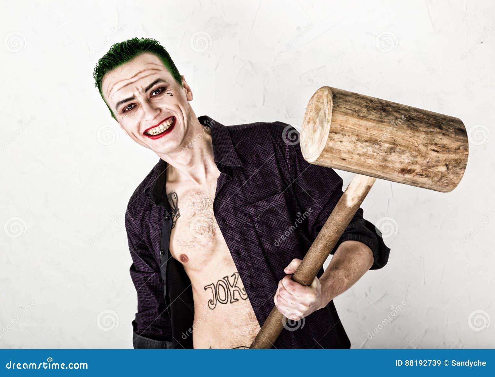 Indivíduo com a cara louca do palhaço, cabelo verde e sorriso idiota traje carnaval guardando o martelo para o grilo