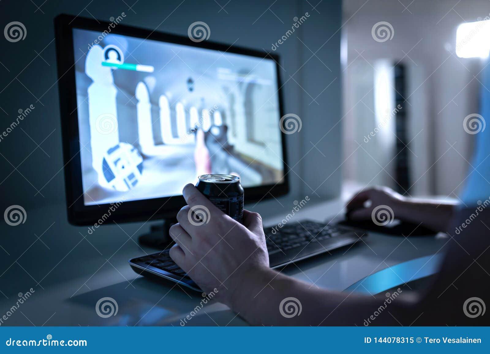 Indivíduo do Gamer que joga o jogo de vídeo e que bebe a bebida da soda ou da energia da lata Videogame de Fps no monitor do comp