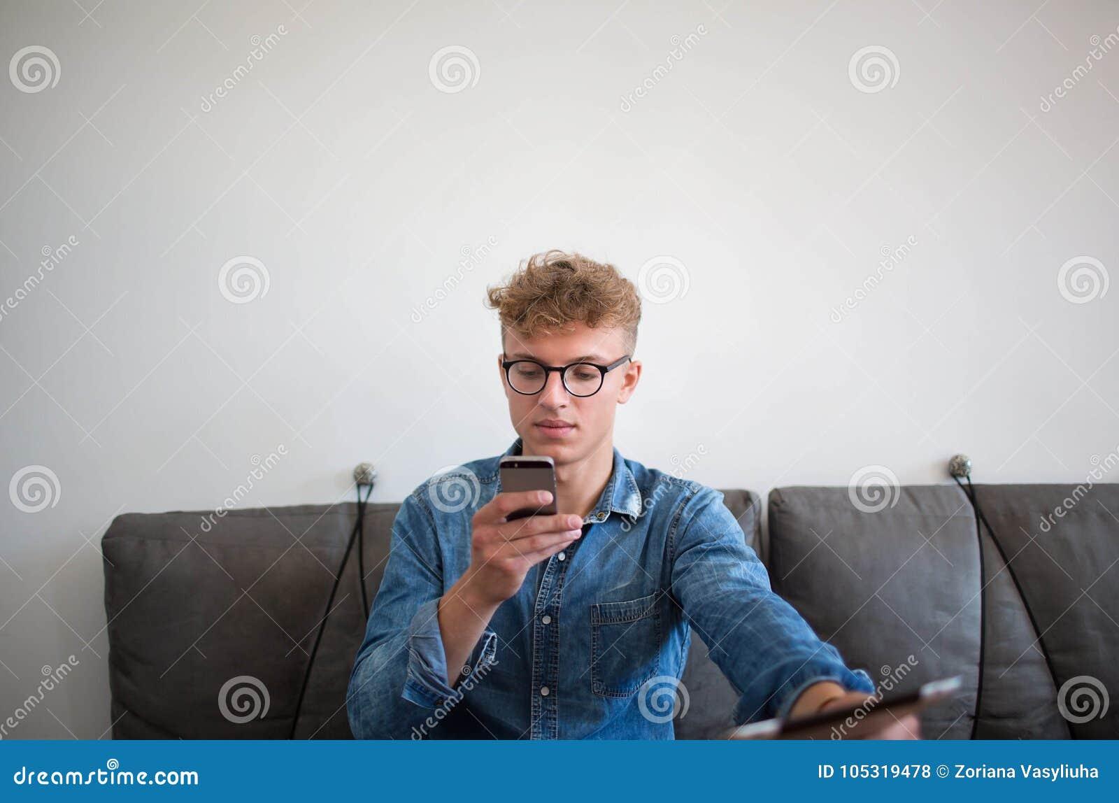 Indivíduo do moderno que envia a mensagem através do telefone celular durante o trabalho na tabuleta digital