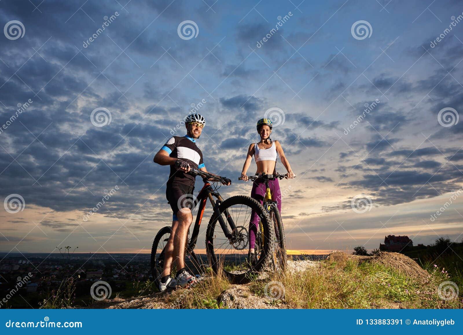 Indivíduo e menina do suporte da constituição dos esportes com as bicicletas na pedra sob o céu de nivelamento nebuloso bonito