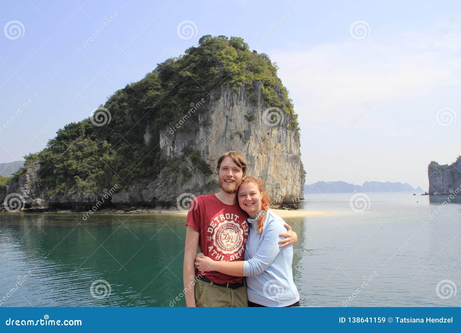 Indivíduo e menina novos dos pares no sportswear que abraça e que ri felizmente na perspectiva dos penhascos da baía longa do Ha