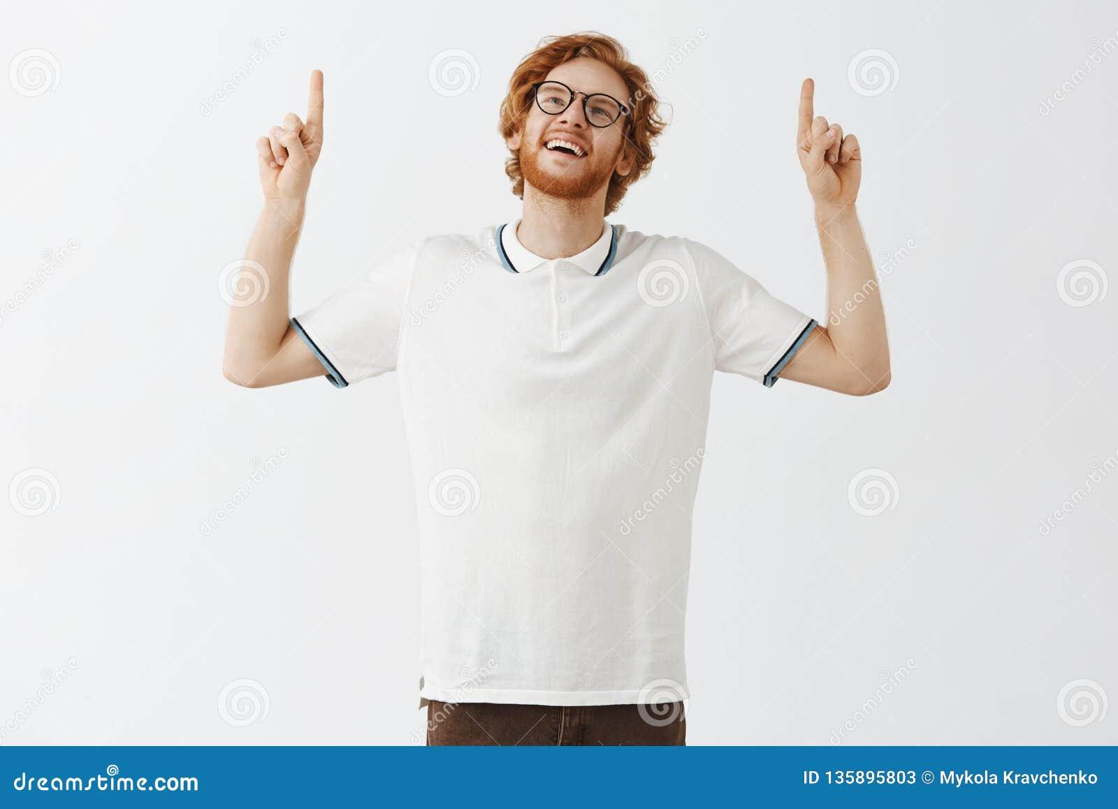 Indivíduo esperto e bonito sonhador do ruivo com a barba que inclina a cabeça para olhar e apontar acima do sorriso com o excpres