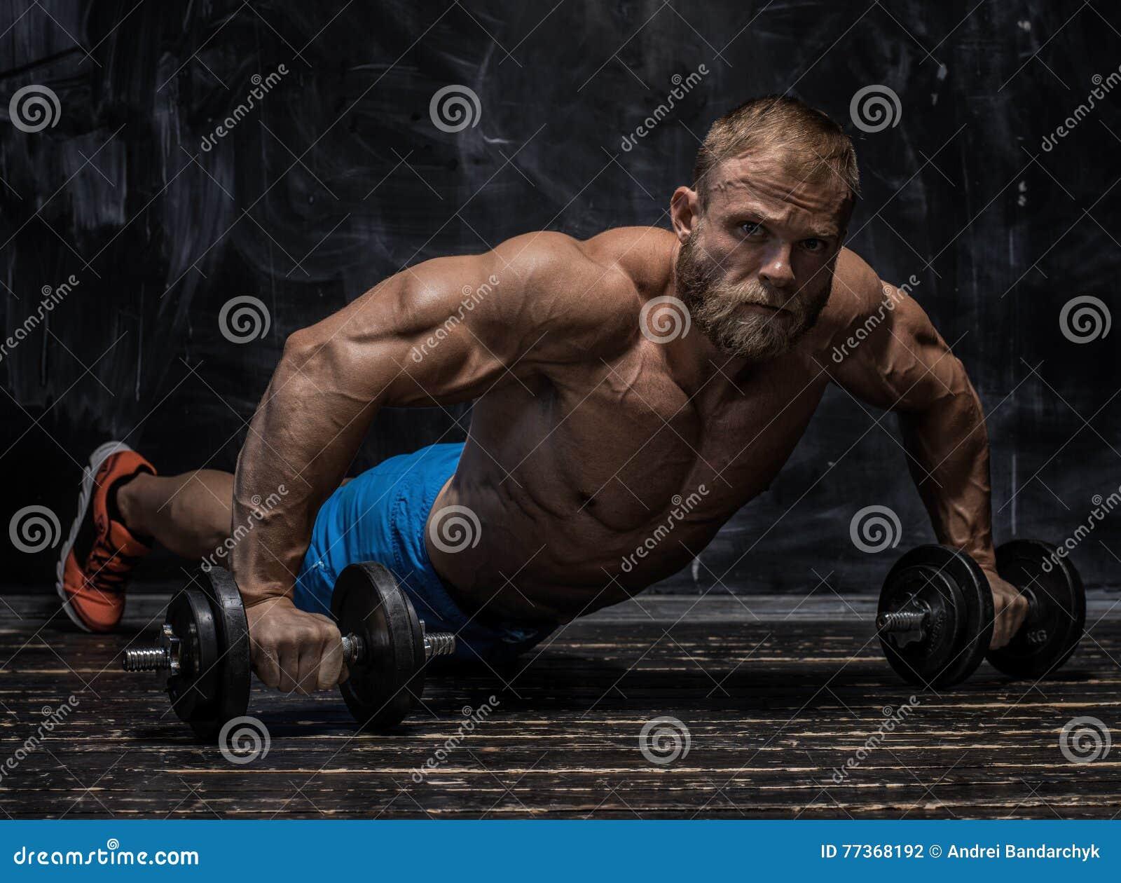 Indivíduo muscular do halterofilista sobre o fundo escuro