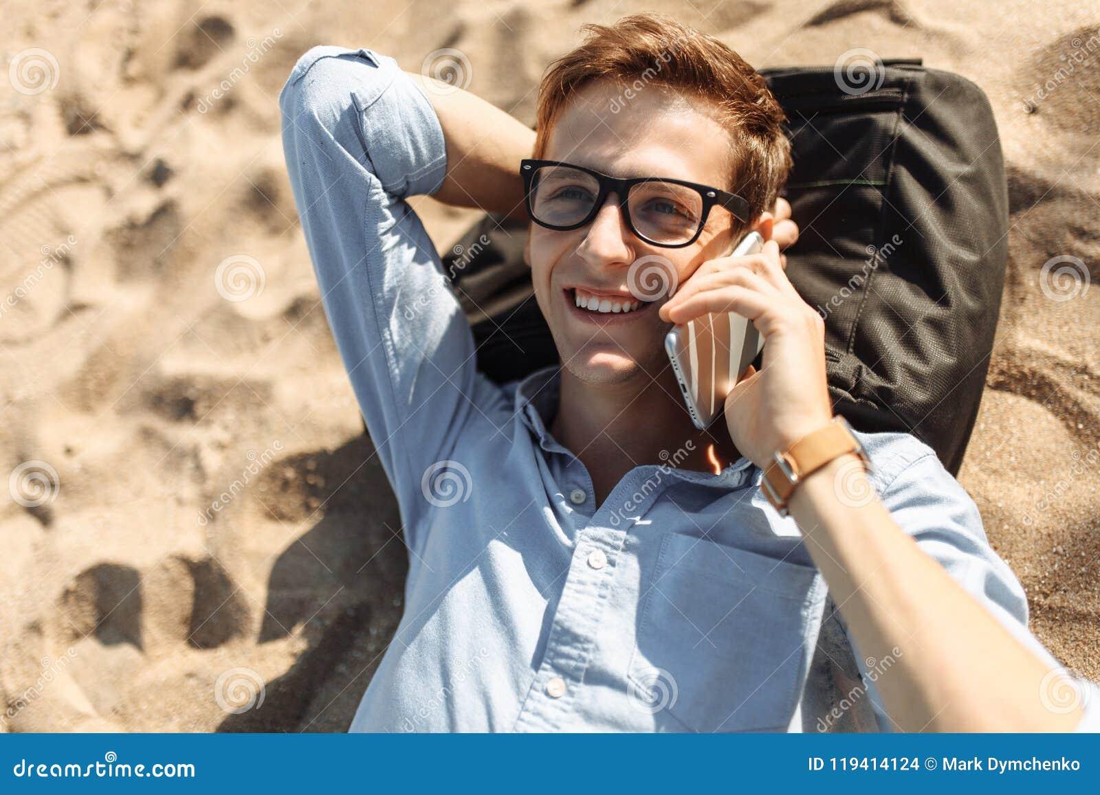 Indivíduo novo com os vidros, encontrando-se na praia na areia, e falando no telefone, trabalho nas férias, apropriadas para anun