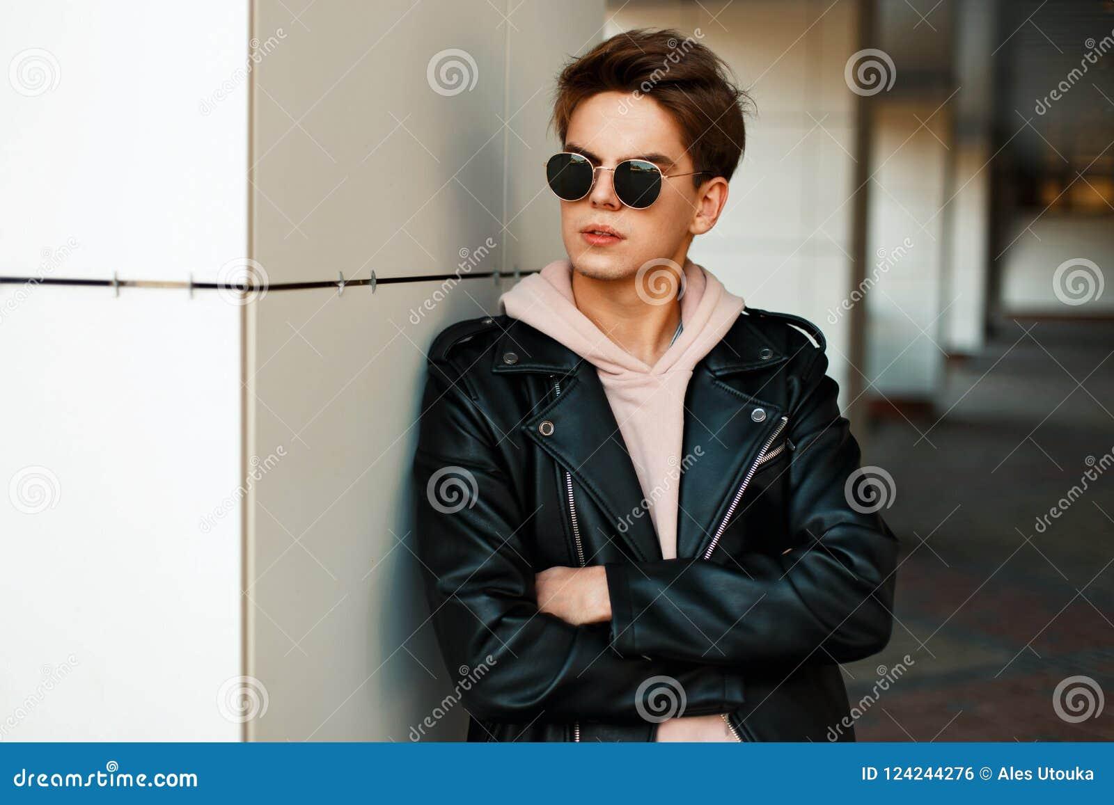 Indivíduo novo considerável com óculos de sol em um elegante marcado