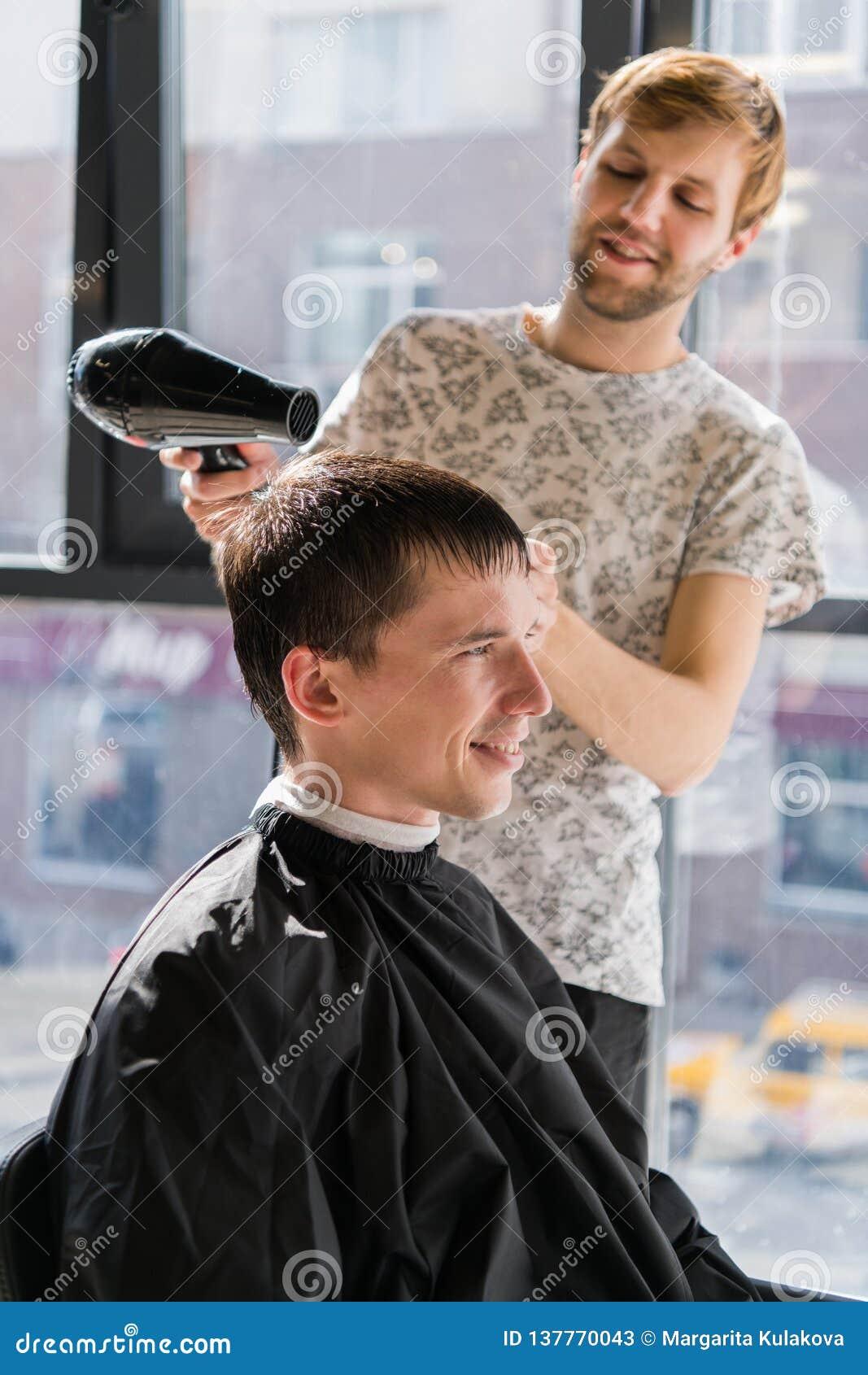 Indivíduo novo na barbearia, cabeleireiro do moderno que corta o cabelo com as tesouras, secando Lugar dos homens do conceito
