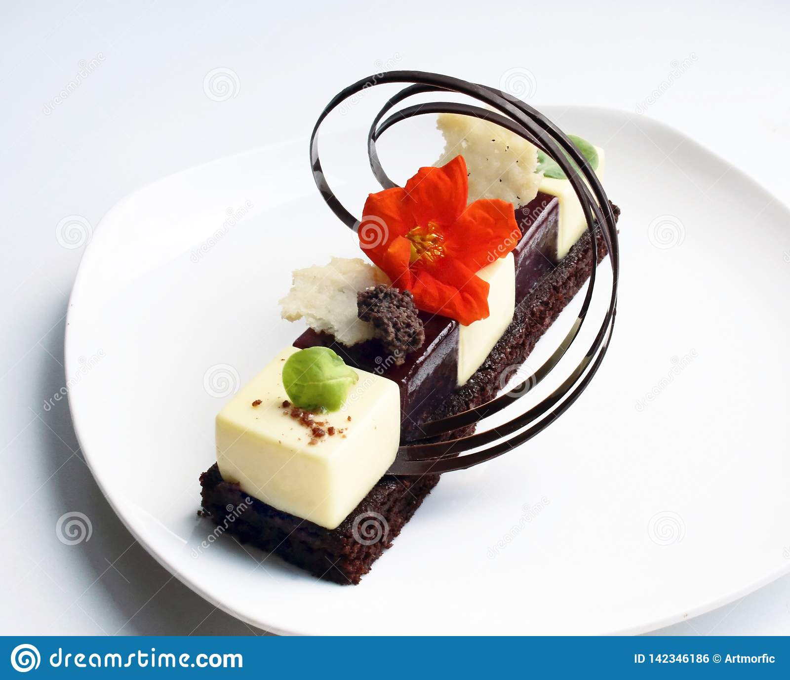 Individual dessert with edible flower and chocolate decoration on white plate