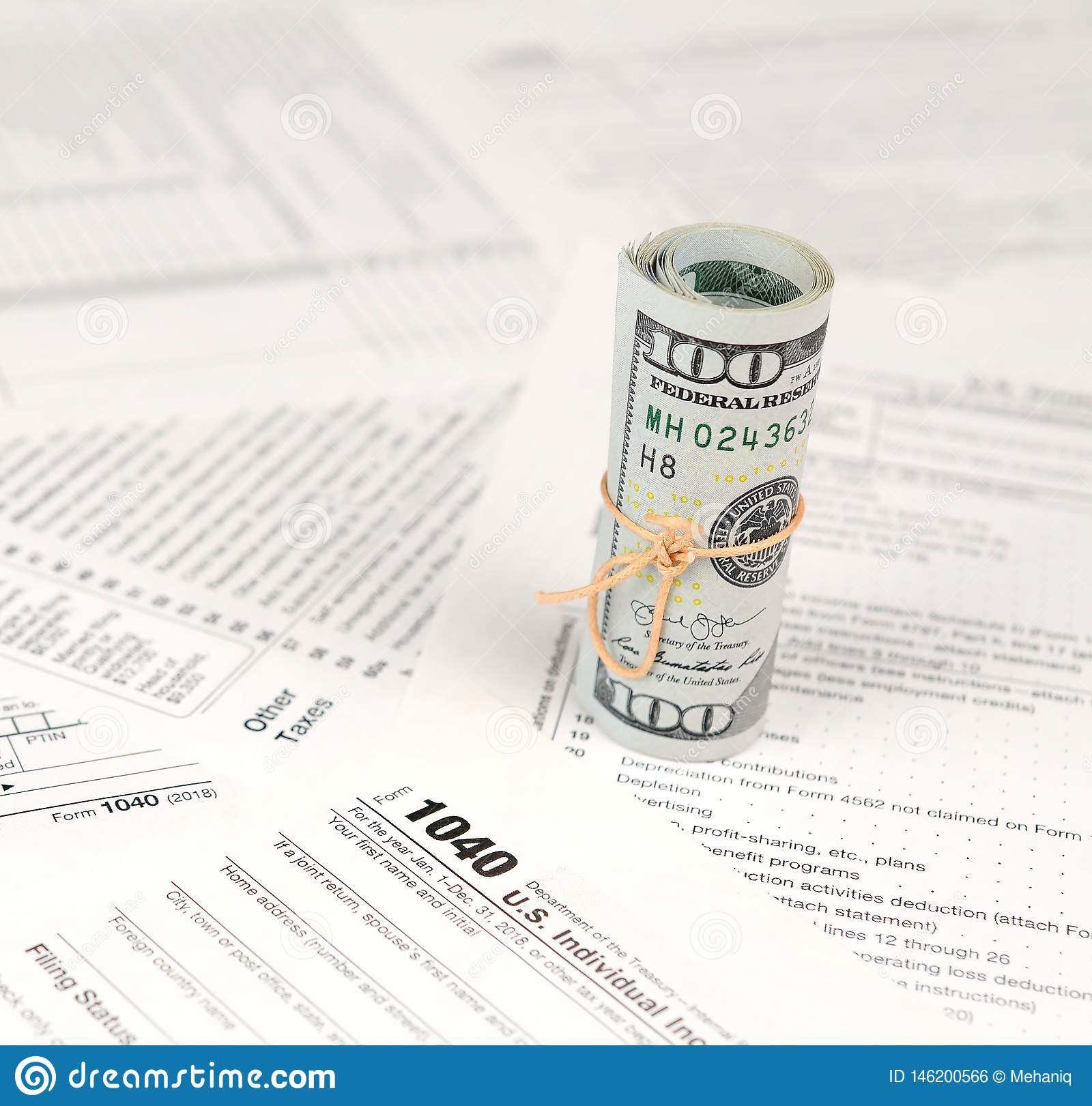 1040 Individual Income Tax Return Form With Roll Of American Dollar Banknotes