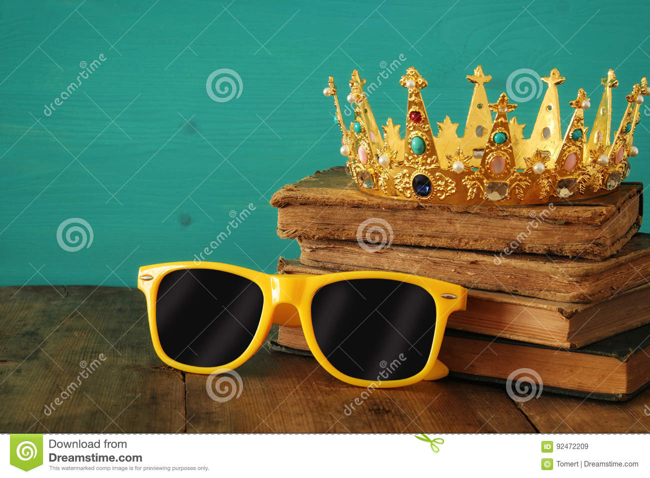 Individuality and unique concept. Old medieval gold crown and cool sunglasses