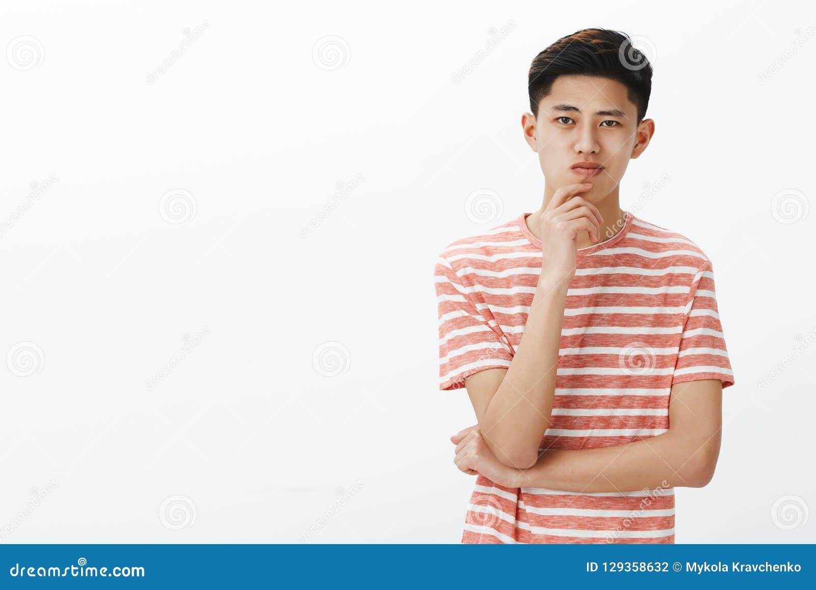 Individuo asiático joven elegante y creativo que piensa en la nueva invención Estudiante masculino chino atractivo resuelto y amb