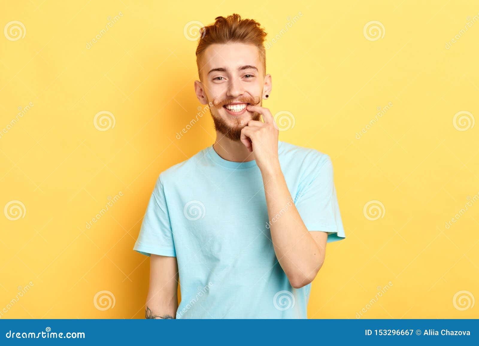 Individuo hermoso joven con la demostración divertida del bigote y el señalar en los dientes blancos