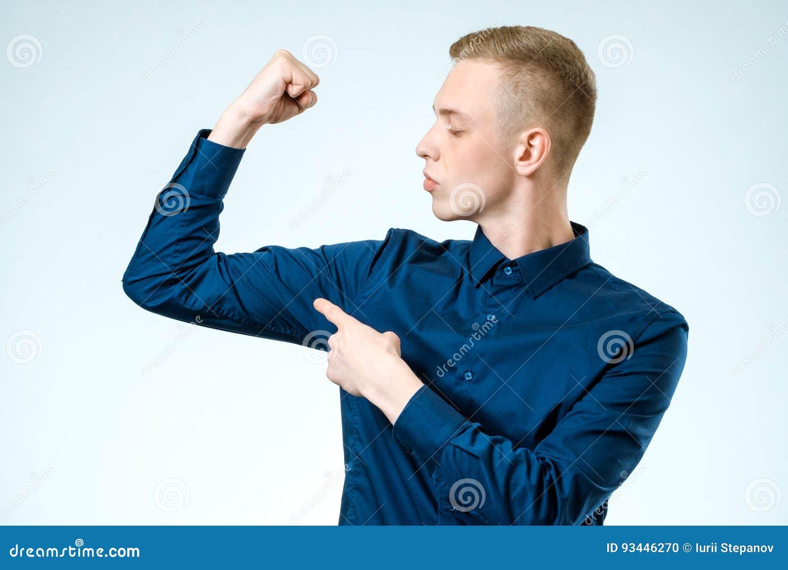 Individuo hermoso joven que señala en su bíceps
