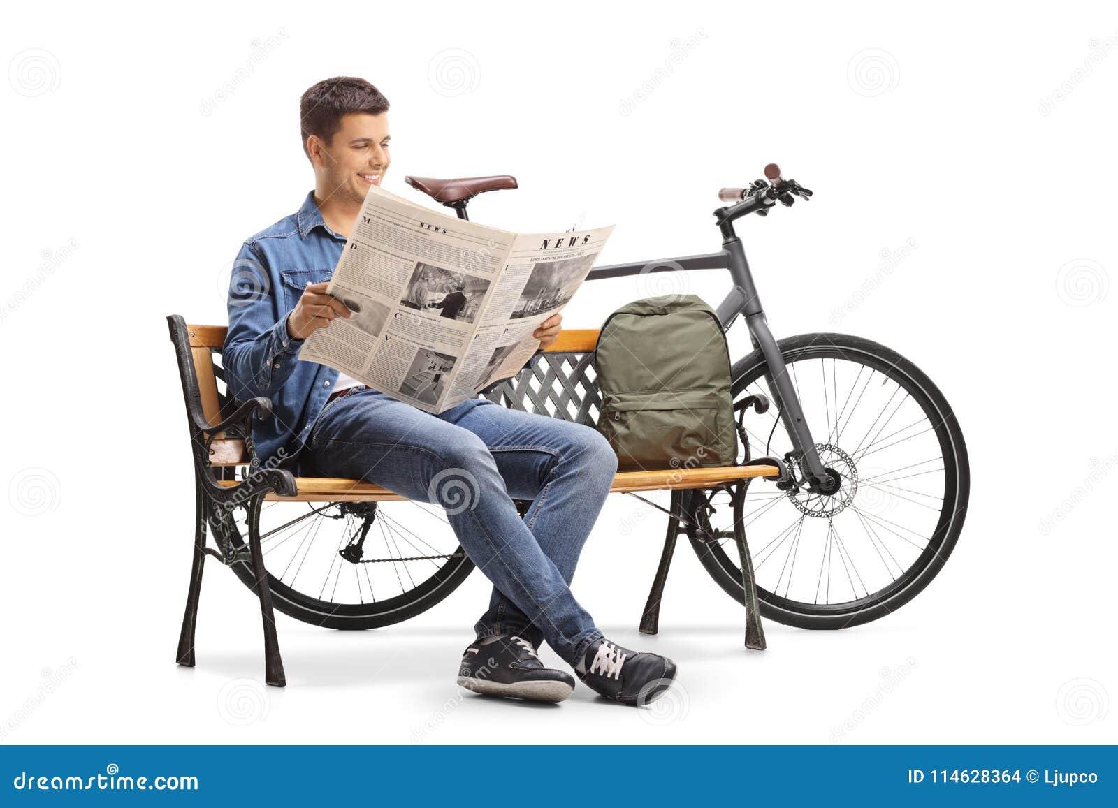 Individuo joven con una bicicleta y una mochila que se sientan en un benc de madera