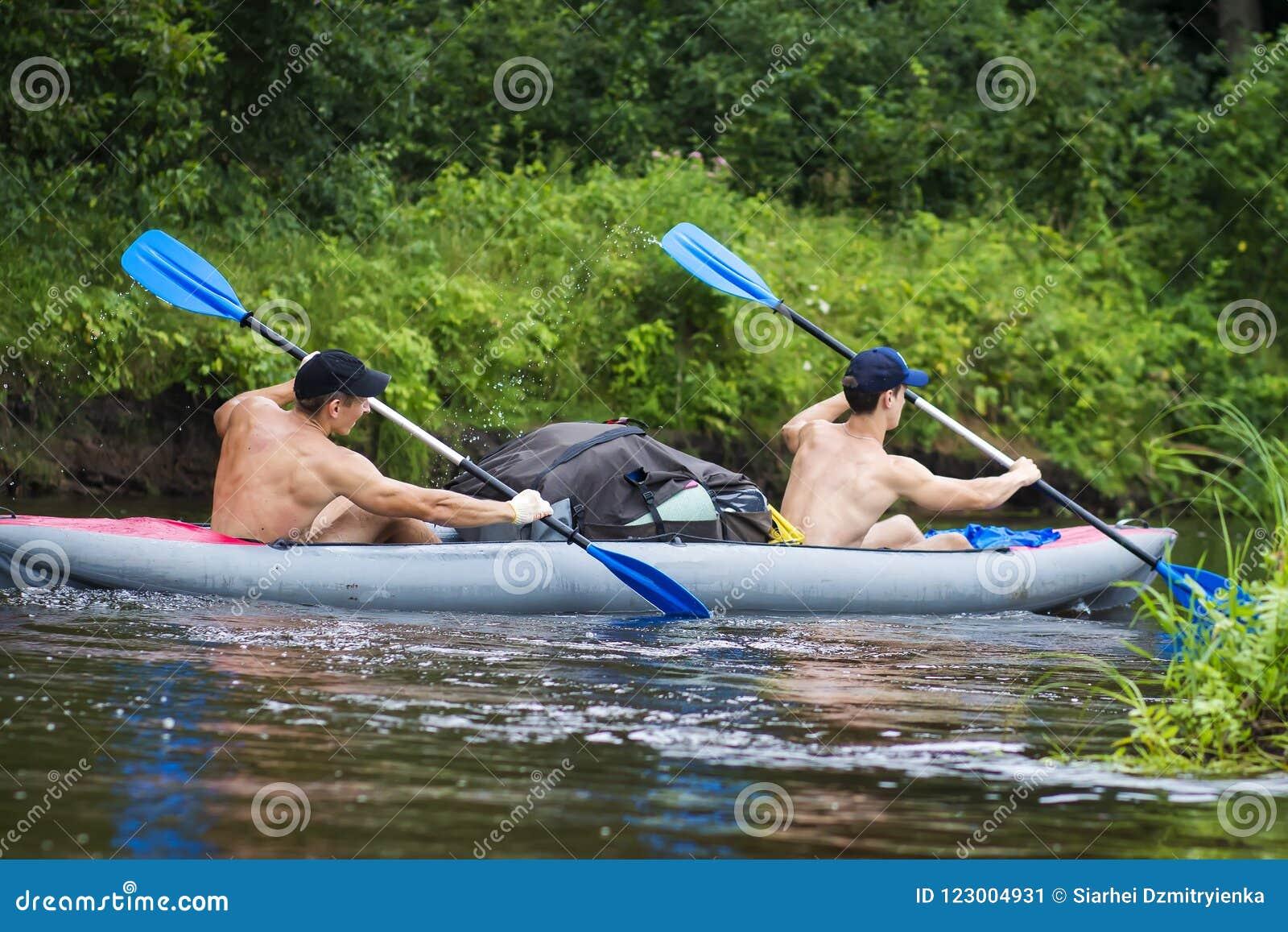 Individuo joven de dos deportes en remos de un rowing del barco en el agua El Kayaking a lo largo del río en la estación de veran