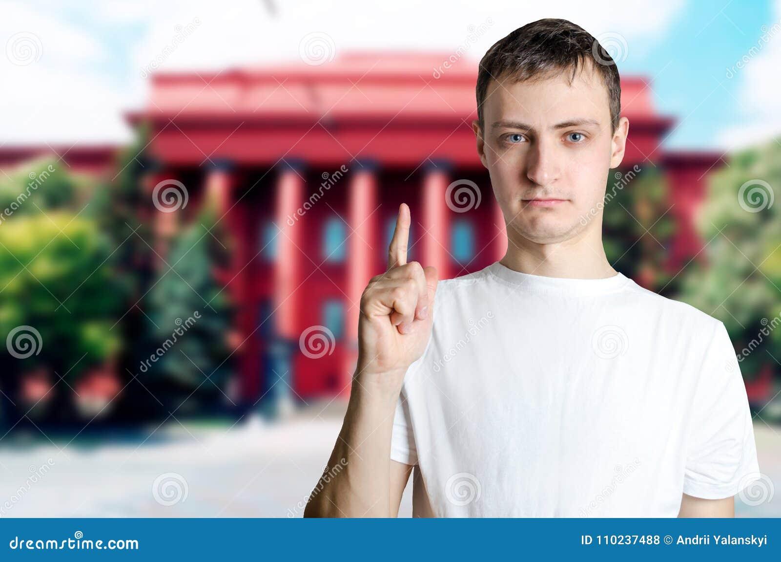 Individuo joven serio que muestra los pulgares para arriba contra el fondo del univer