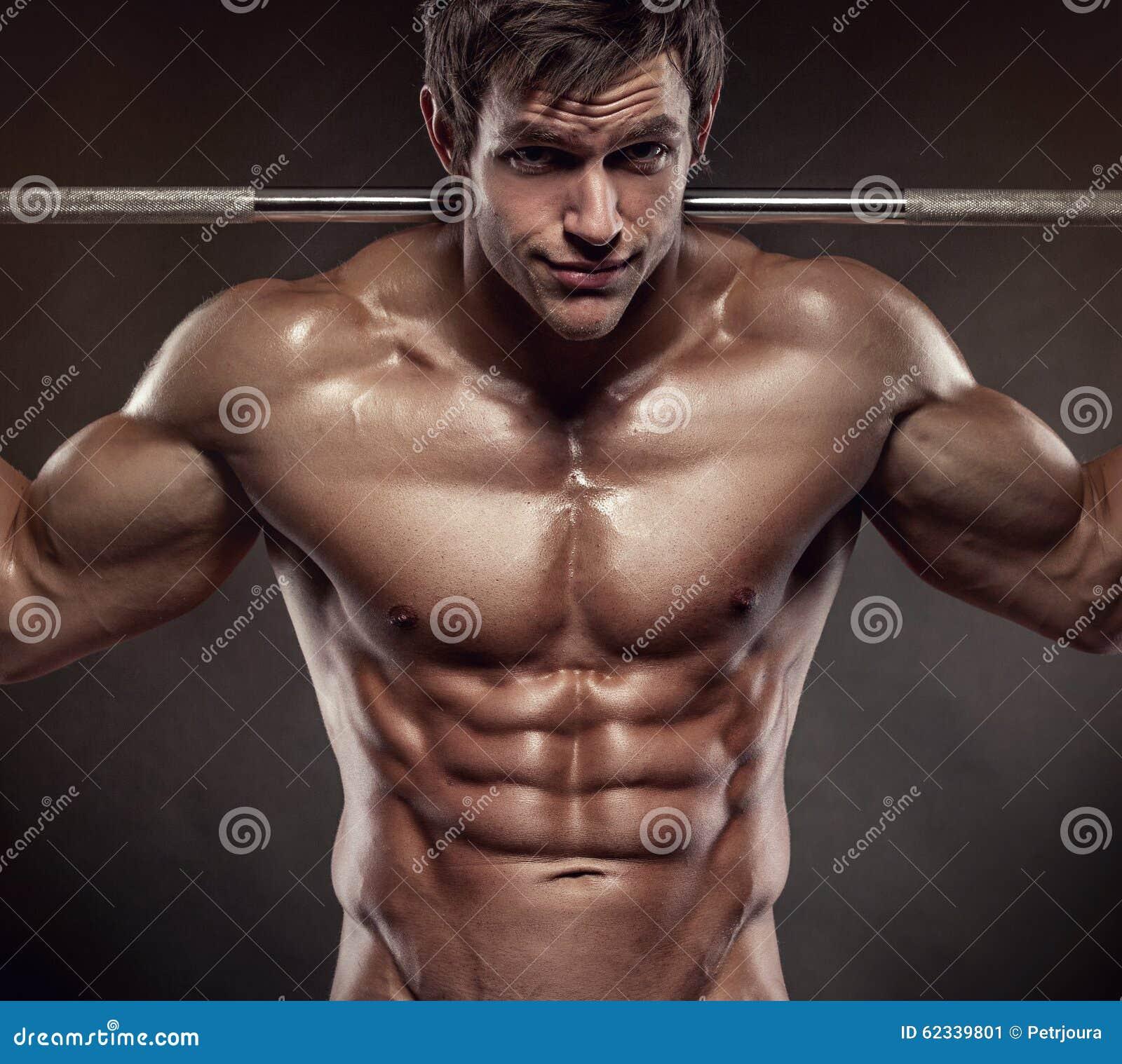 Individuo muscular del culturista que hace ejercicios con pesas de gimnasia sobre bla