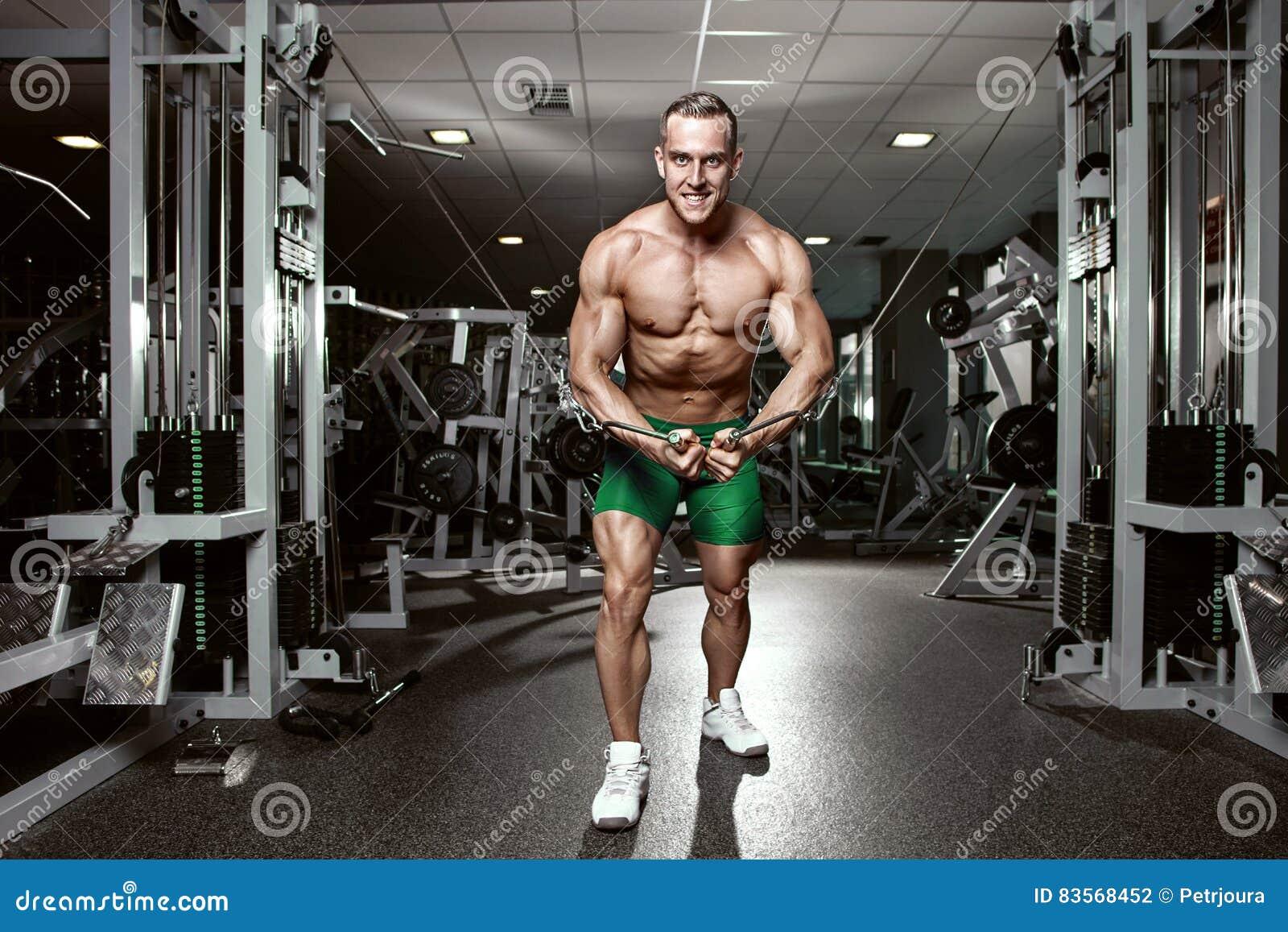 Individuo muscular del culturista que hace entrenamiento de los ejercicios en gimnasio
