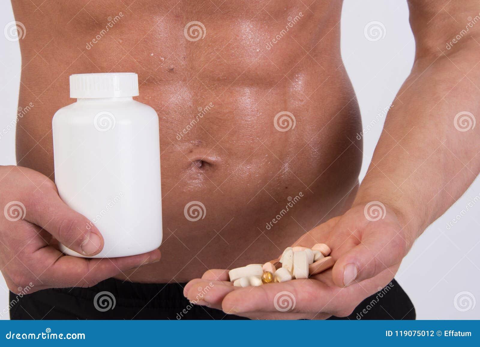 Individuo muscular joven Se divierte la nutrición Acepta las tabletas después de entrenar