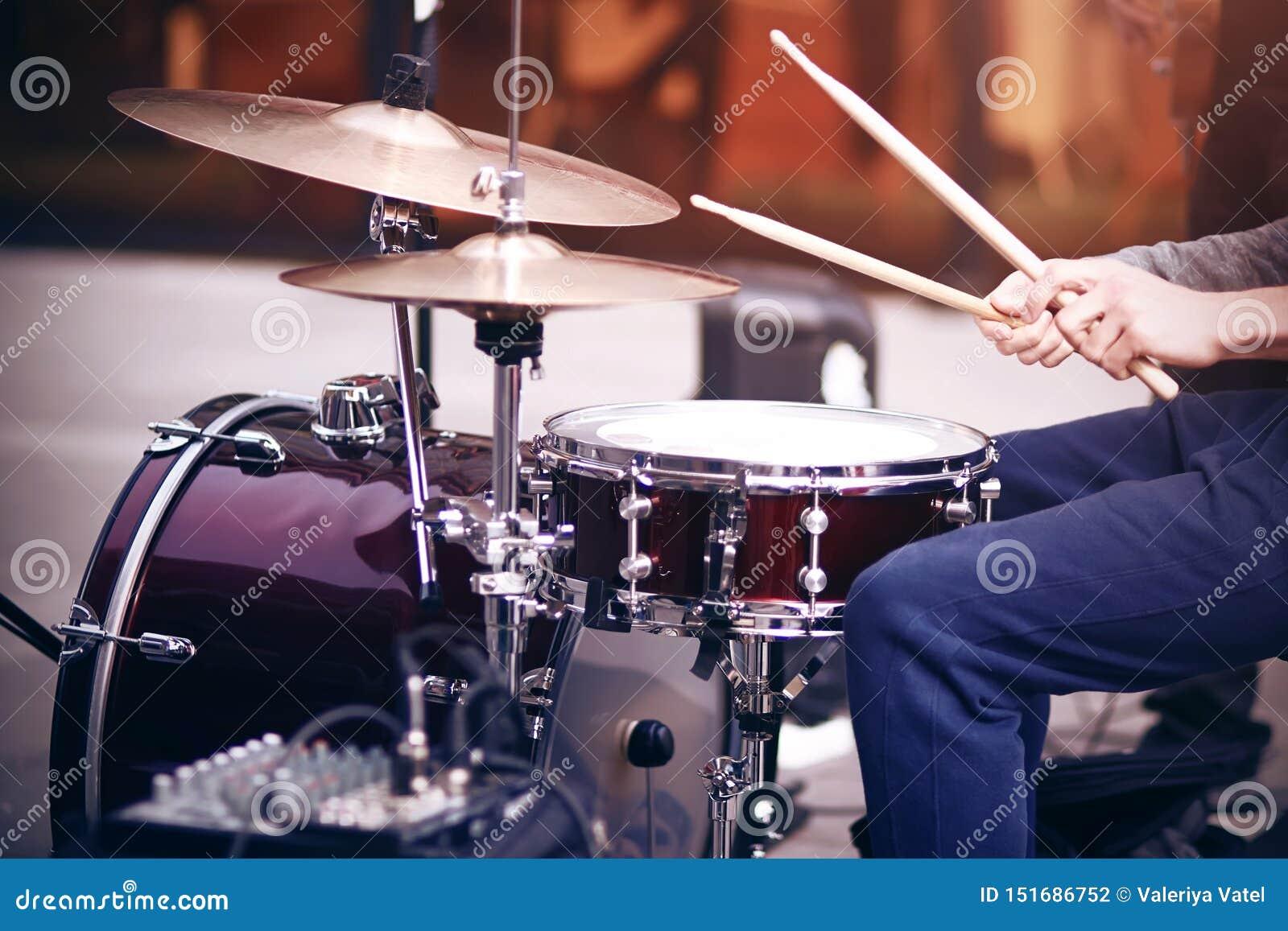 Individuo que juega ritmo en un tambor rojo fijado con los palillos