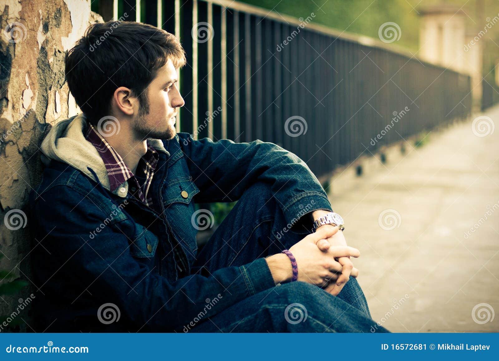 Individuo que se sienta cerca de la cerca