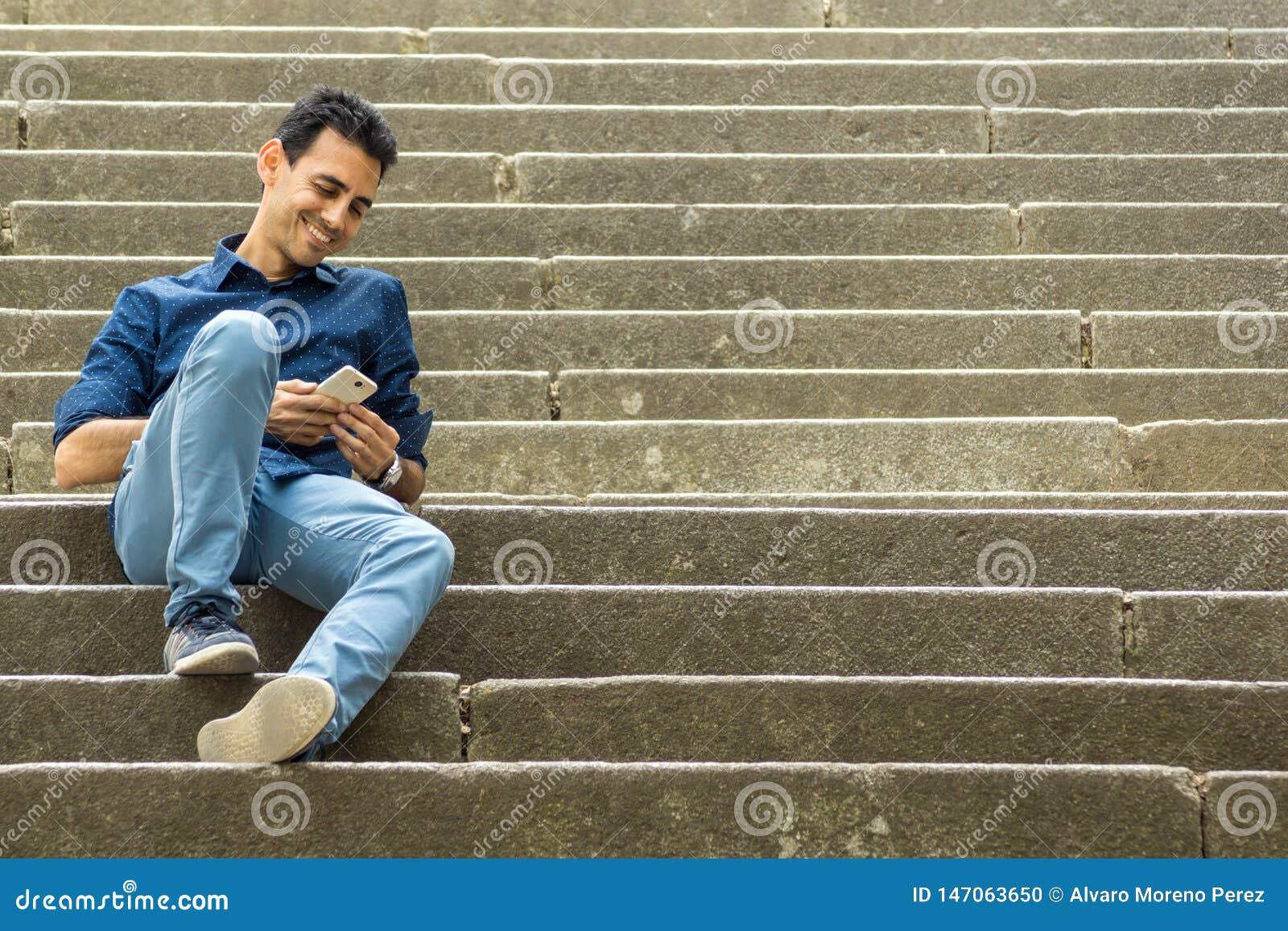 Individuo que se sienta en las escaleras con smartphone