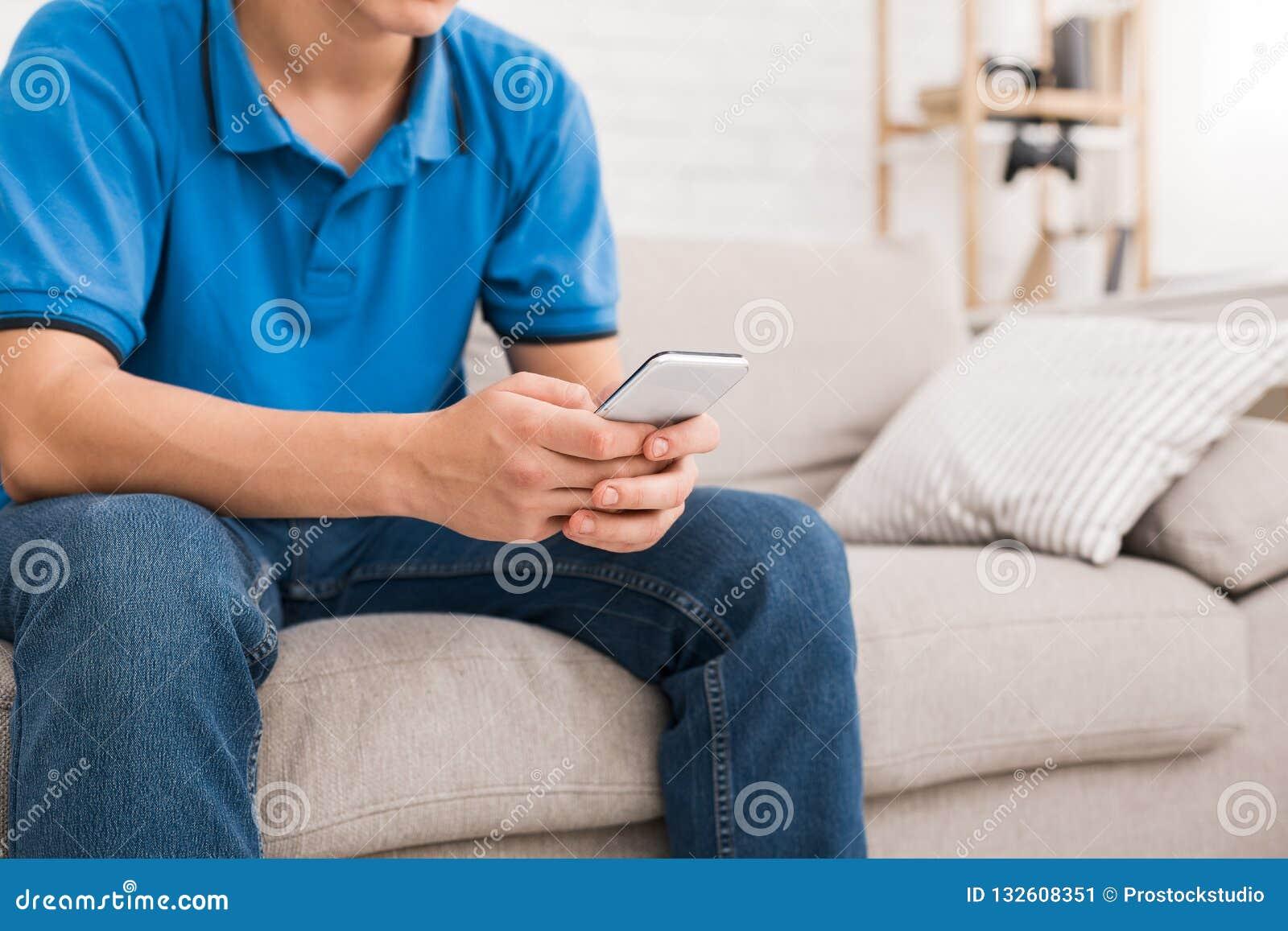 Individuo que usa smartphone mientras que se sienta en el sofá